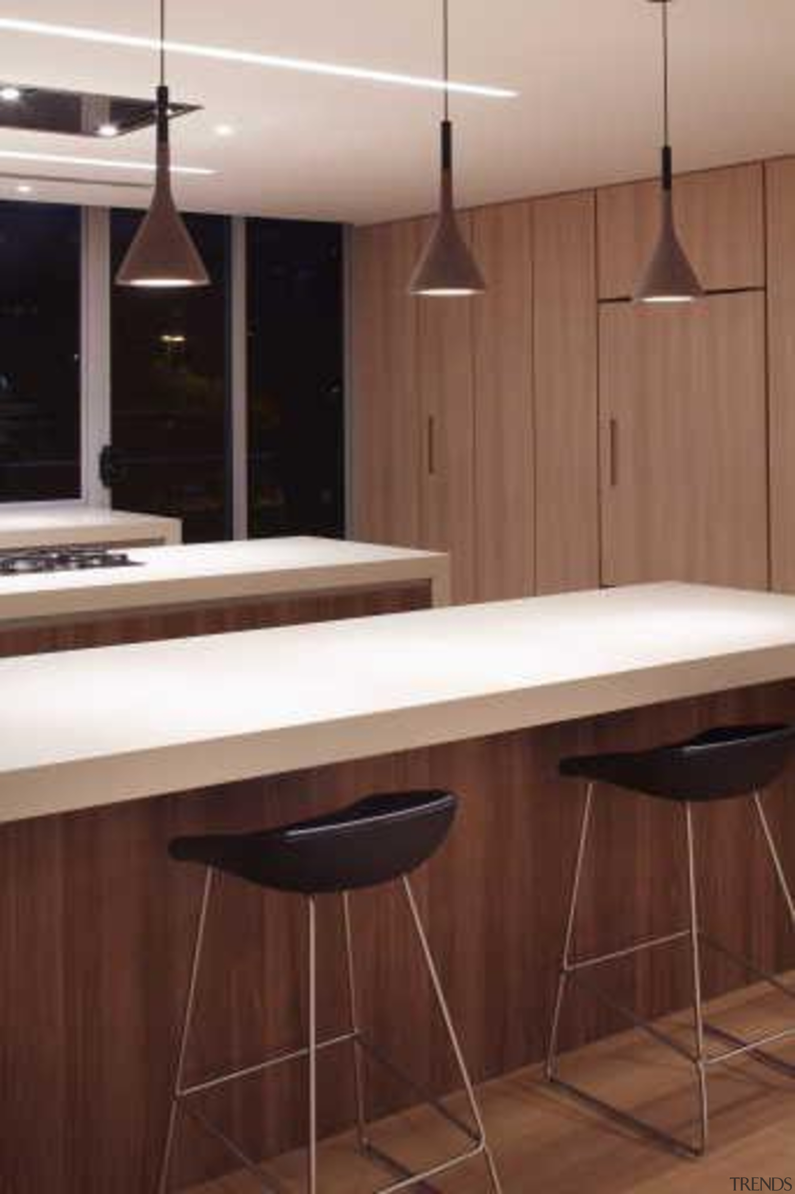 In this contemporary apartment renovation, woodgrain surfaces from cabinetry, countertop, floor, flooring, furniture, interior design, kitchen, lighting, product design, room, table, wood, brown, red