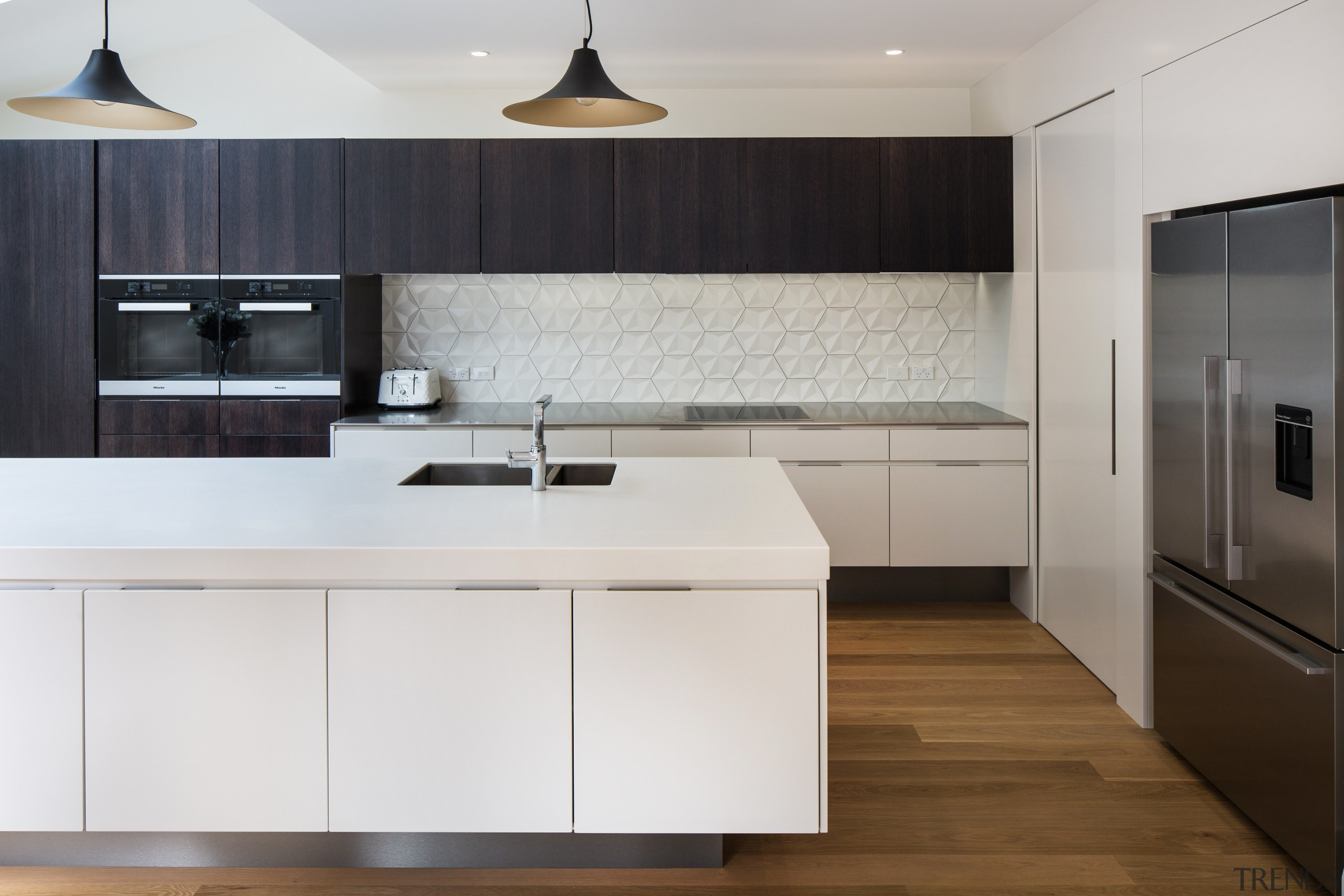 Contrasting the mainly crisp, clean surfaces, the splashback cabinetry, countertop, cuisine classique, floor, home appliance, interior design, kitchen, product design, room, wood flooring, gray