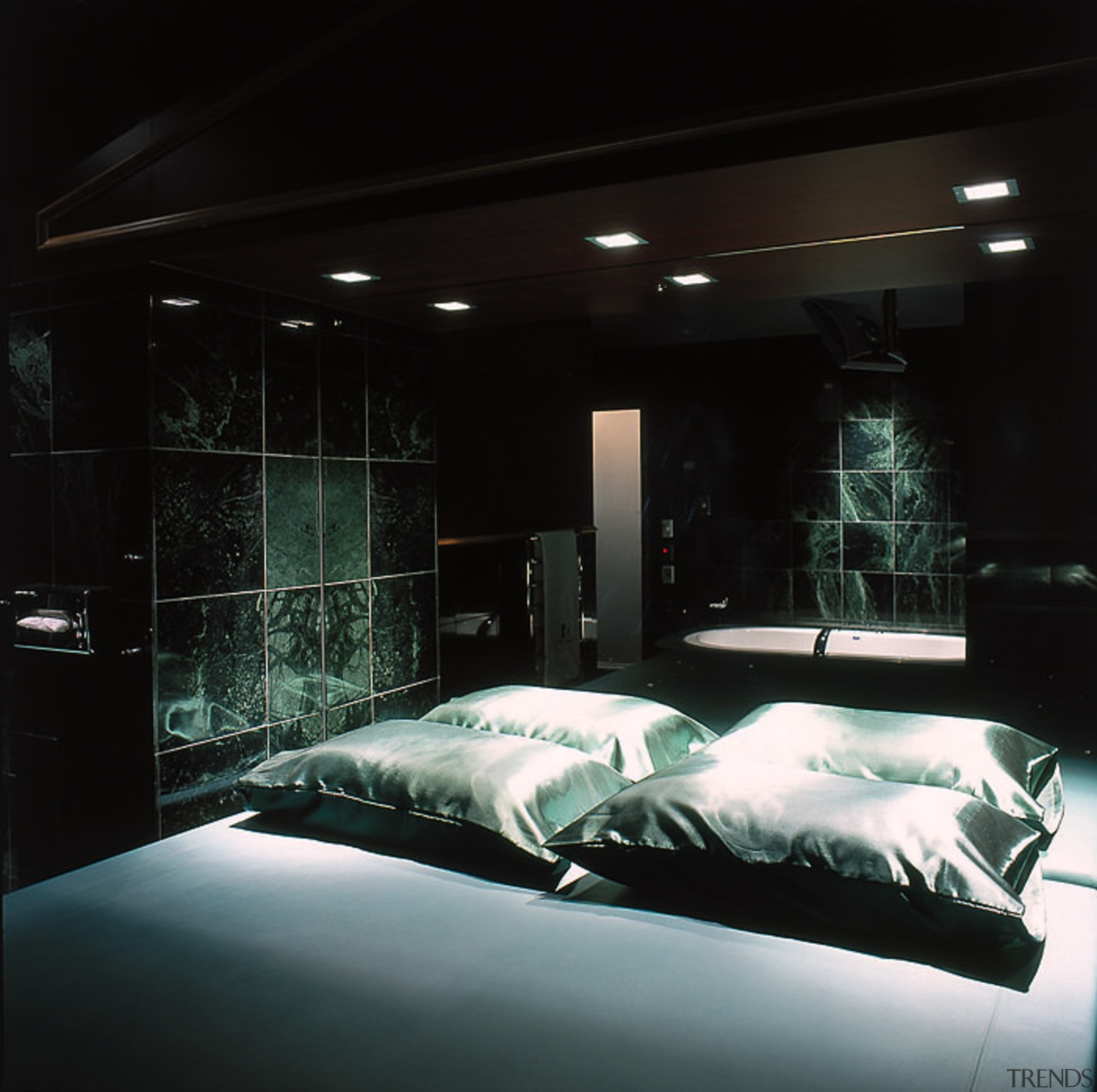 Bedroom With Black Pillows And Bedding Dark Green Marble Tiles On Walls White Bath In Background