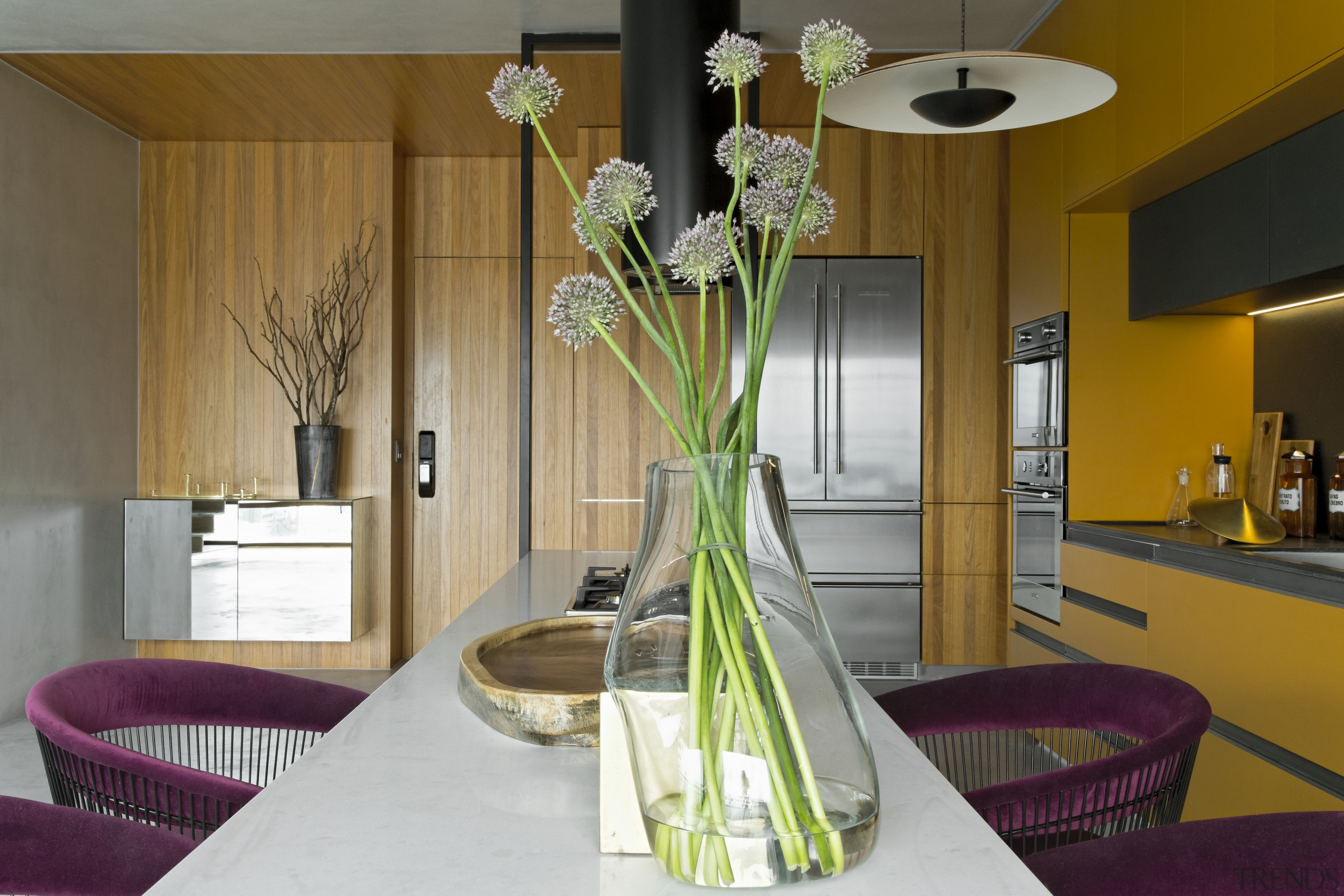 Contemporary kitchen with suspended island, warm-toned cabinetry and building, dining room, flower, furniture, home, house, interior design, plant, property, real estate, room, suite, table, vase, yellow, brown, gray