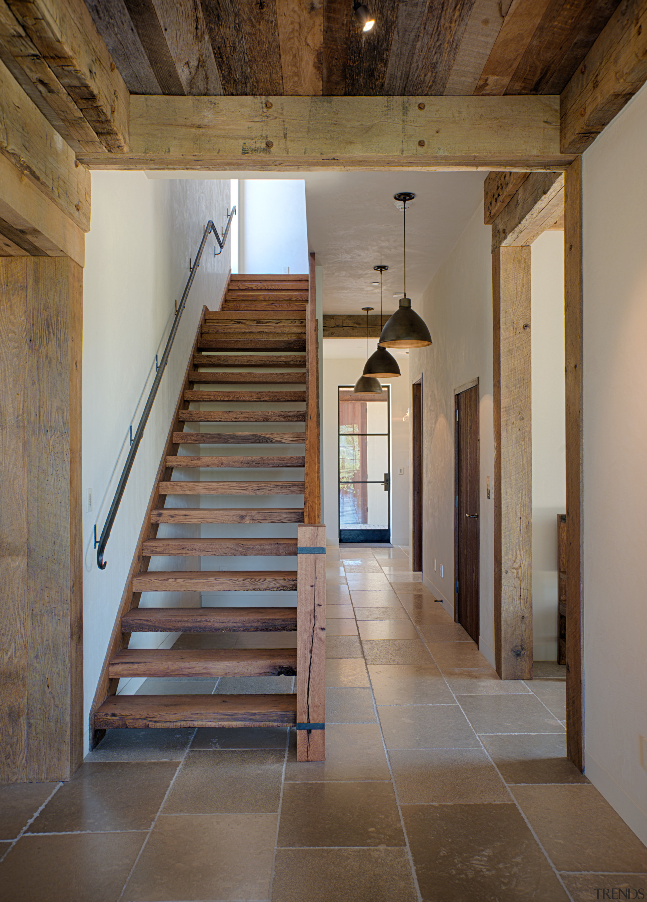 Designer Julian Cohen used French limestone flooring with apartment, architecture, beam, daylighting, floor, flooring, handrail, home, house, interior design, stairs, structure, wall, wood, brown, gray