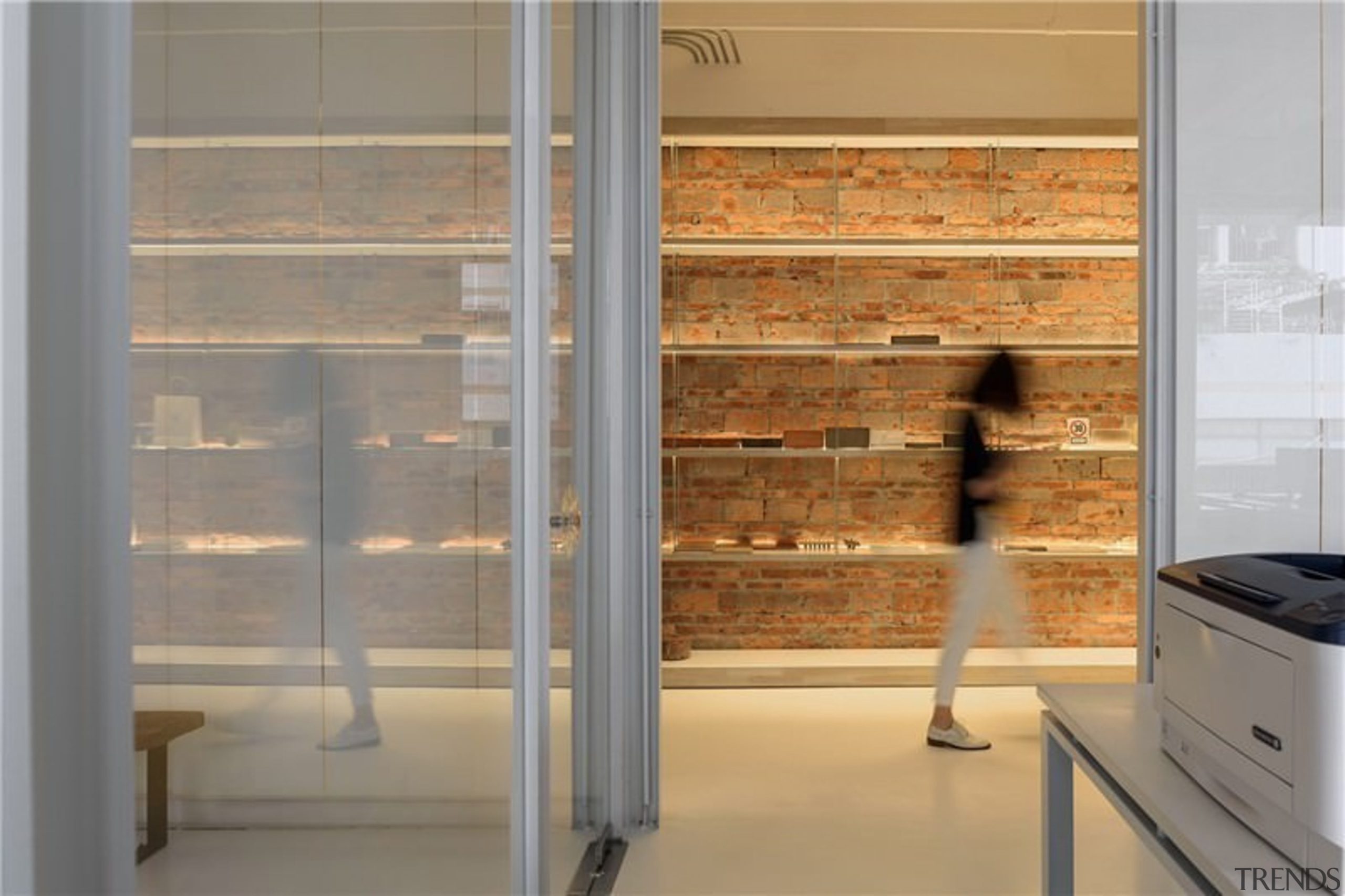 A brick wall serves as a place to cabinetry, display case, floor, interior design, window, gray