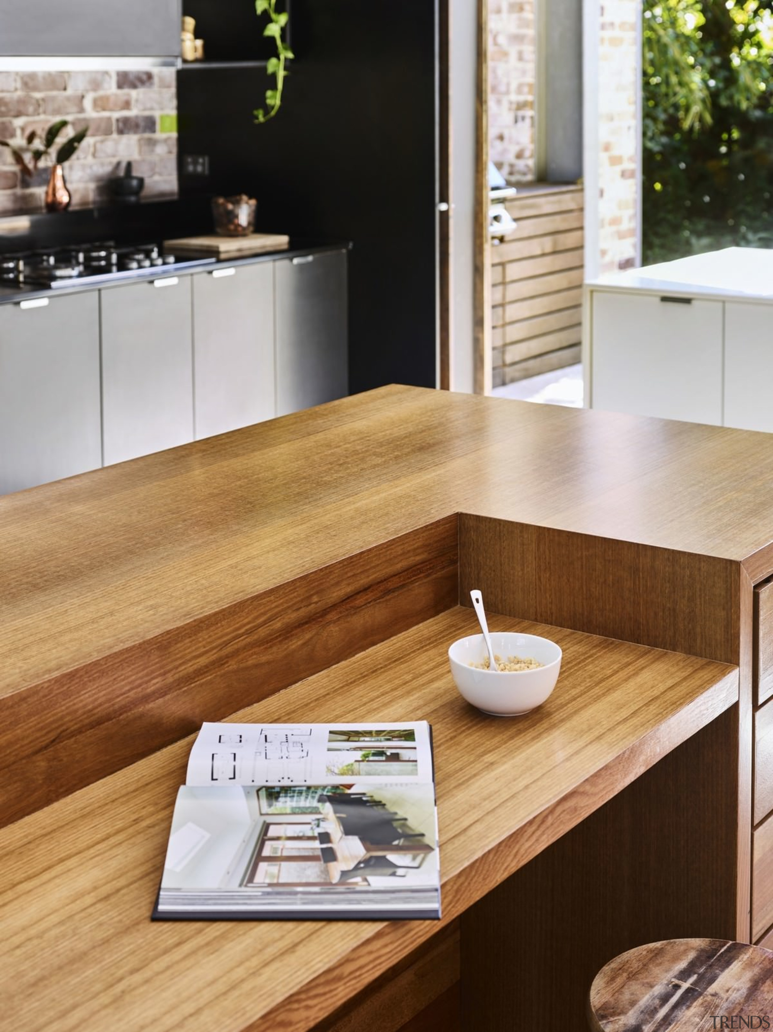 The wooden kitchen island stands apart from the countertop, floor, flooring, furniture, hardwood, interior design, kitchen, product design, table, wood, wood flooring, brown