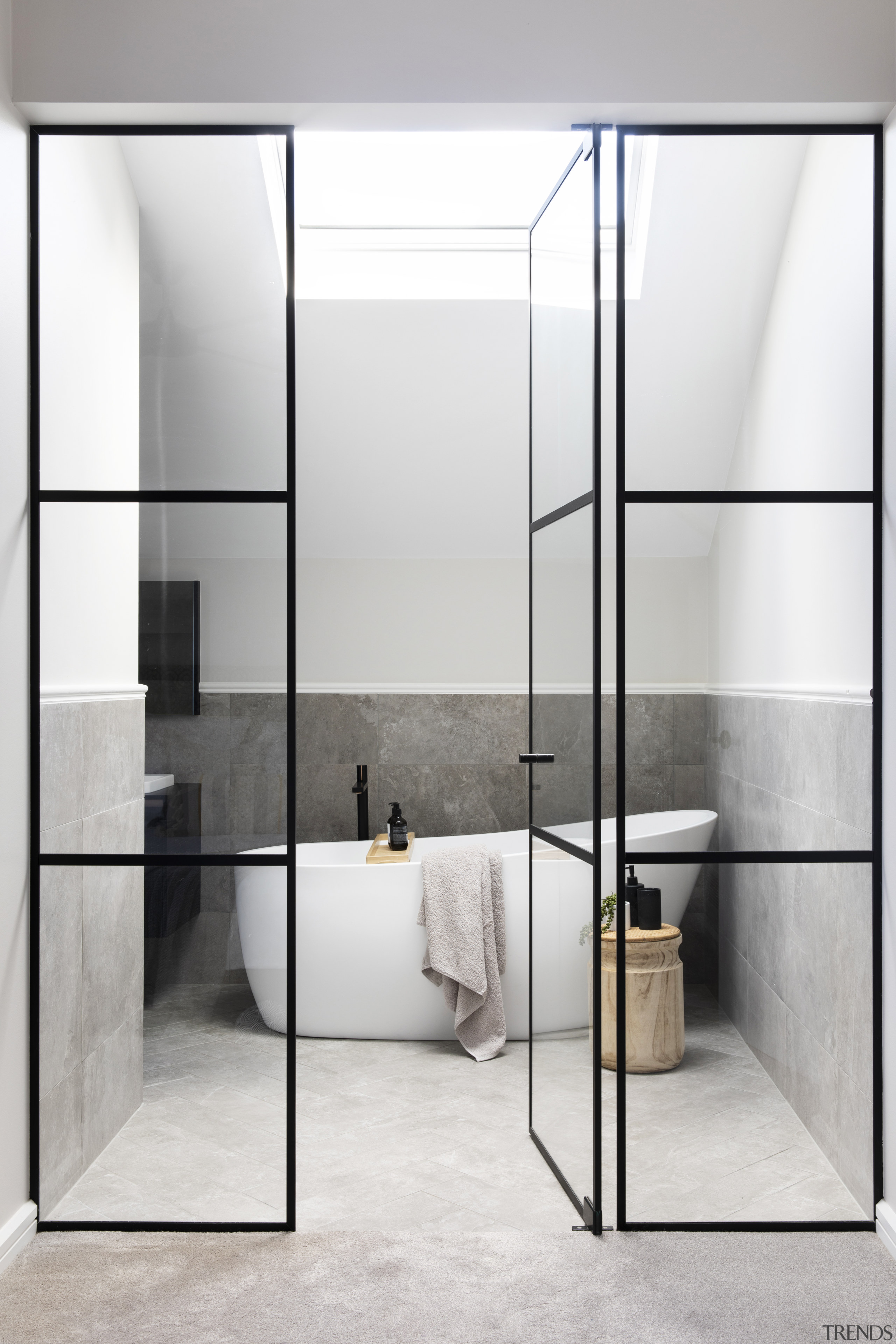 A black-framed glass wall leads to the light-filled