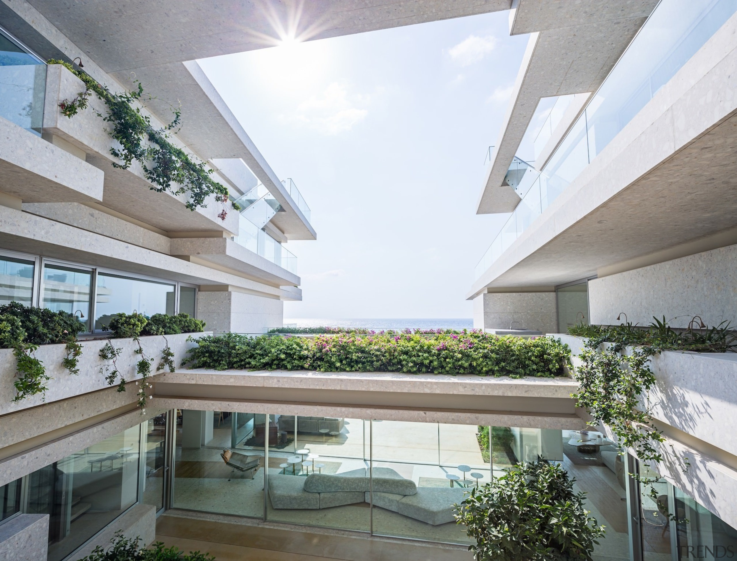 This large courtyard opens up to the sea apartment, architecture, balcony, condominium, courtyard, daylighting, daytime, estate, facade, home, house, interior design, mixed use, property, real estate, residential area, roof, window, white, gray