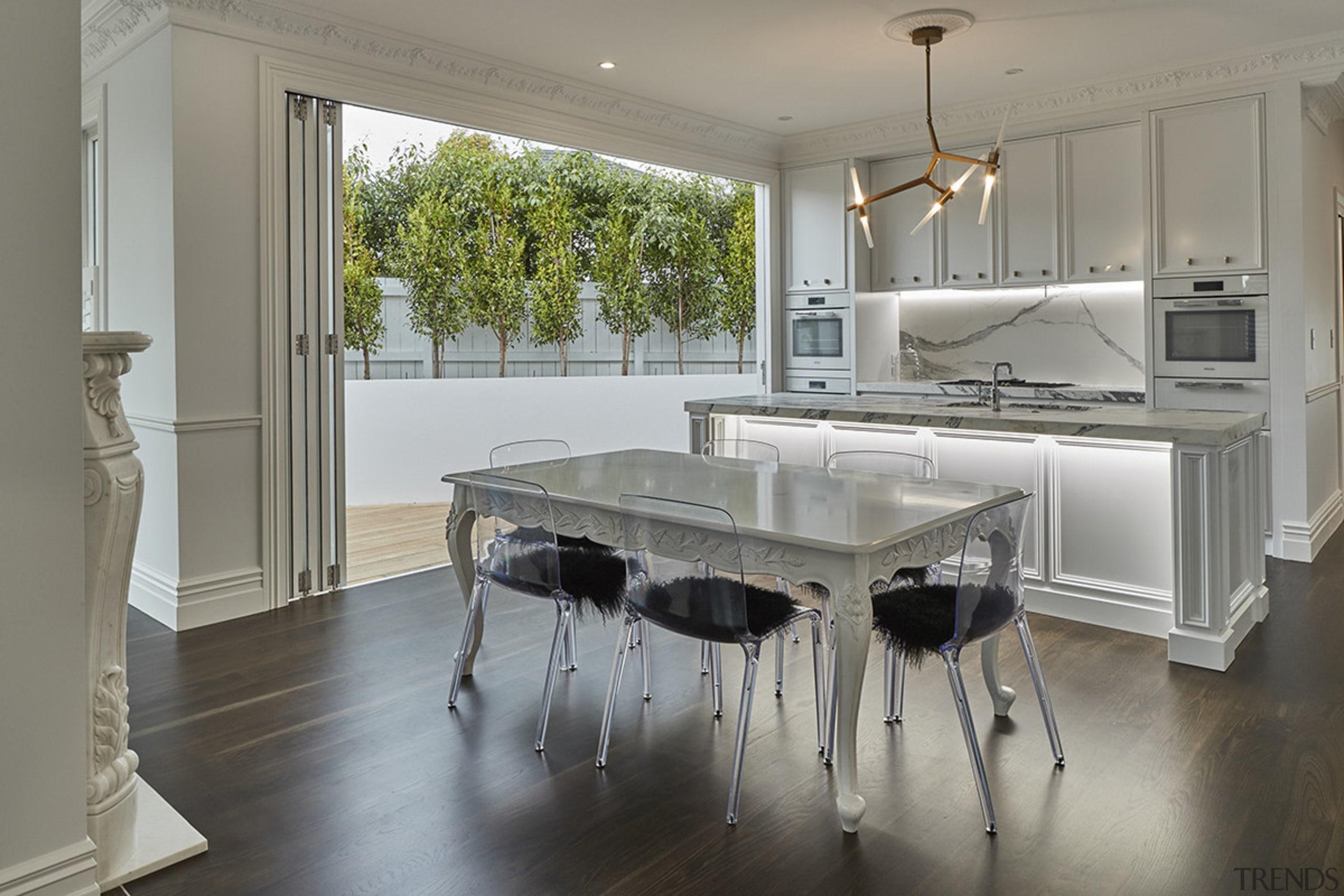 Part of a transformative villa renovation, this central, countertop, floor, flooring, interior design, kitchen, real estate, table, gray