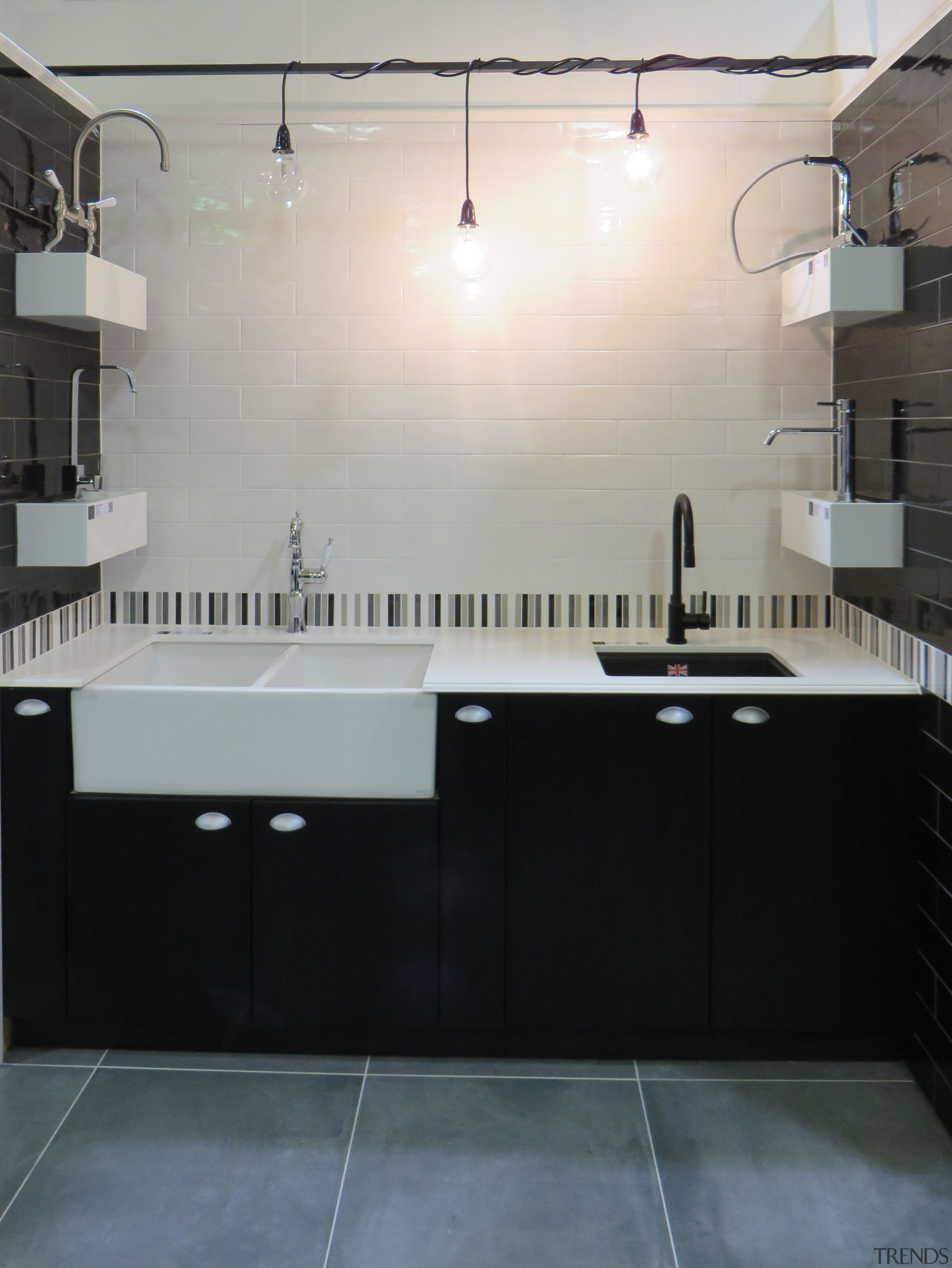 The displays encourage visitors to try out the bathroom, cabinetry, countertop, floor, flooring, glass, interior design, kitchen, property, sink, tile, gray, black