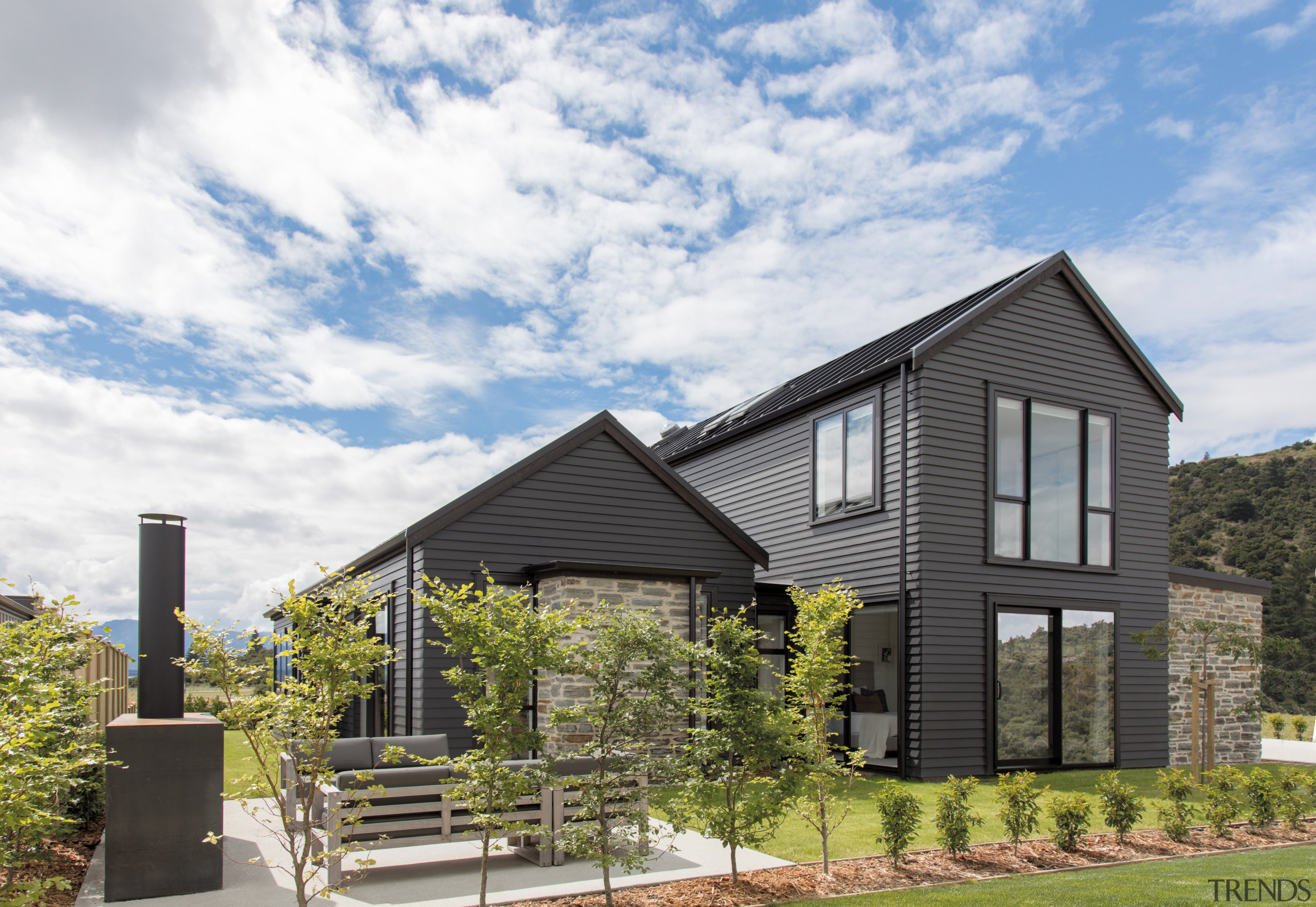 Dark tones and stone cladding elements give this architecture, building, cloud, cottage, estate, facade, farmhouse, grass, home, house, land lot, landscape, neighbourhood, property, real estate, residential area, roof, rural area, siding, sky, suburb, tree, white