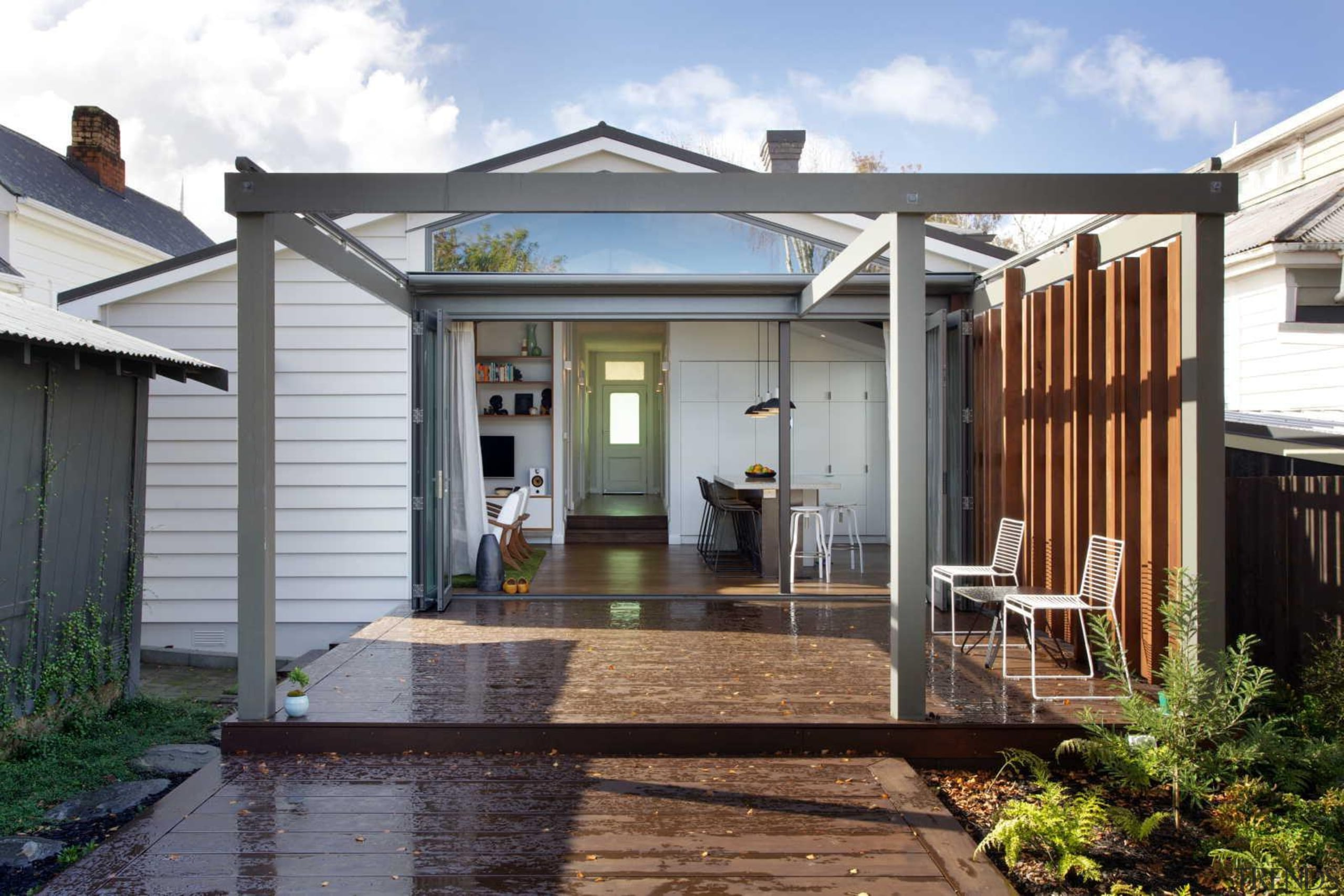 The large timber deck and pergola define the backyard, cottage, deck, estate, facade, home, house, outdoor structure, porch, property, real estate, roof, siding, white