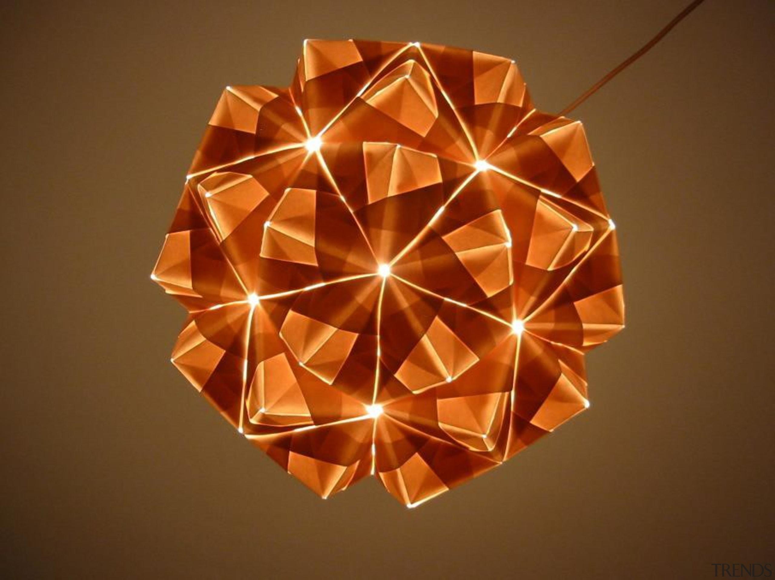 A range of folded metallic fabrics  are lampshade, light fixture, lighting, lighting accessory, origami, symmetry, brown