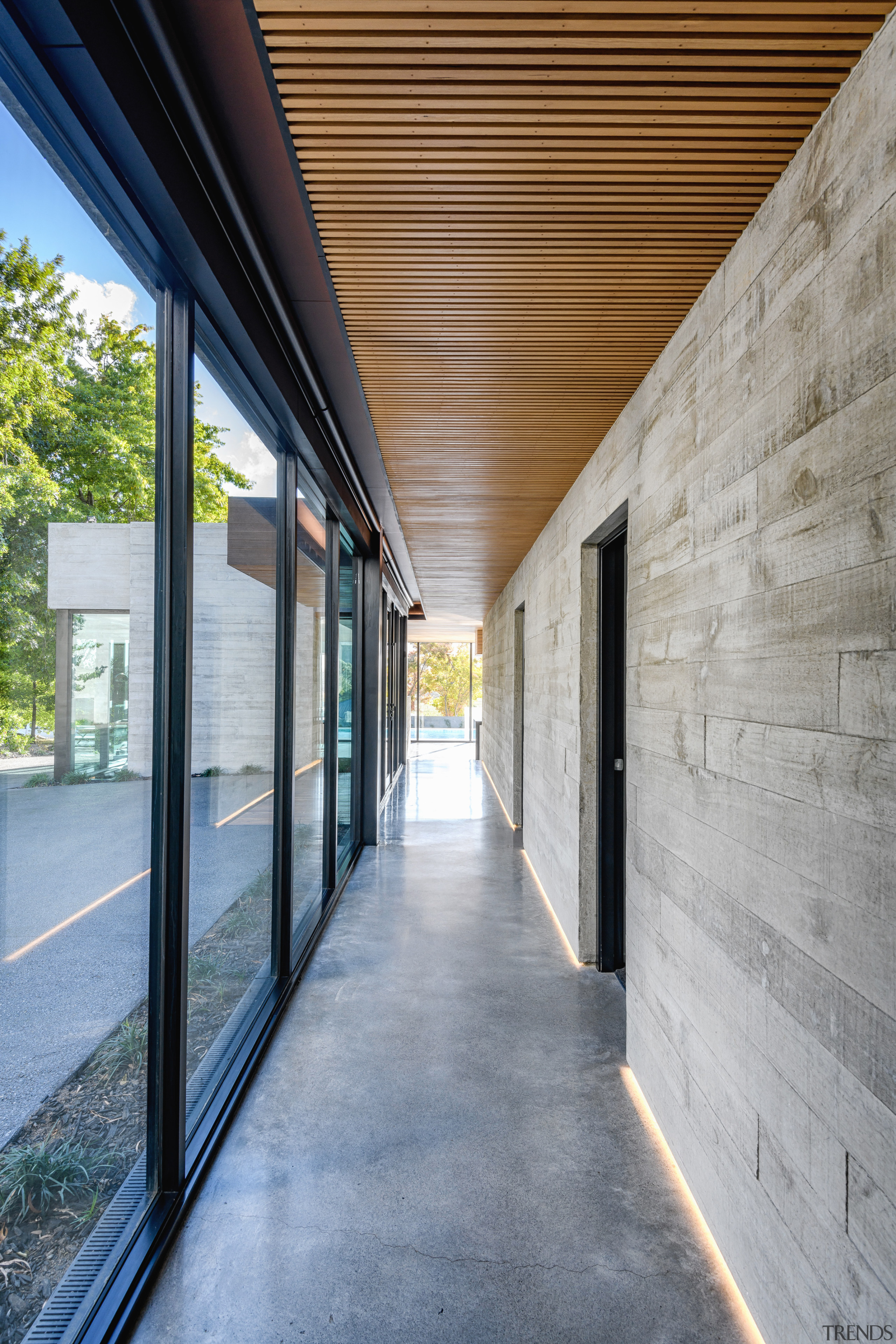 A long look down this home's connecting corridor architecture, brick, building, ceiling, concrete, daylighting, facade, floor, glass, hall, home, house, interior design, line, property, real estate, shade, walkway, wall, window, gray