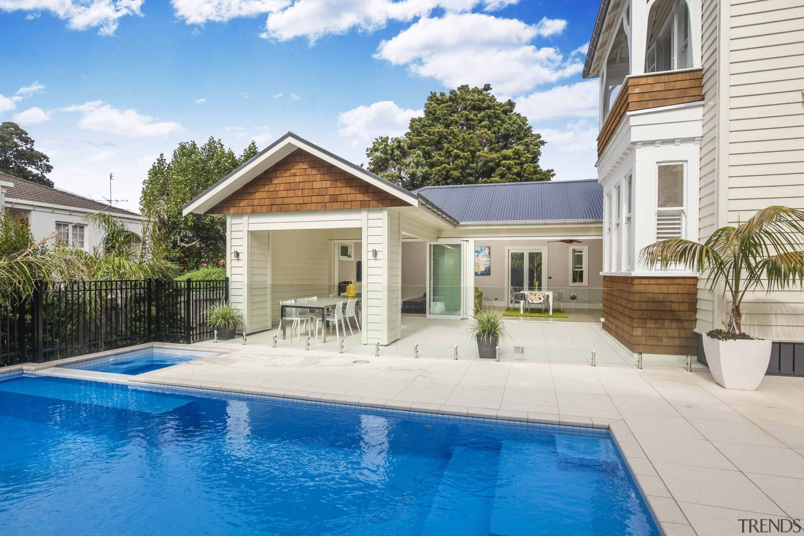 The swimming pool features a connected spa pool backyard, cottage, estate, facade, home, house, property, real estate, residential area, swimming pool, villa, white