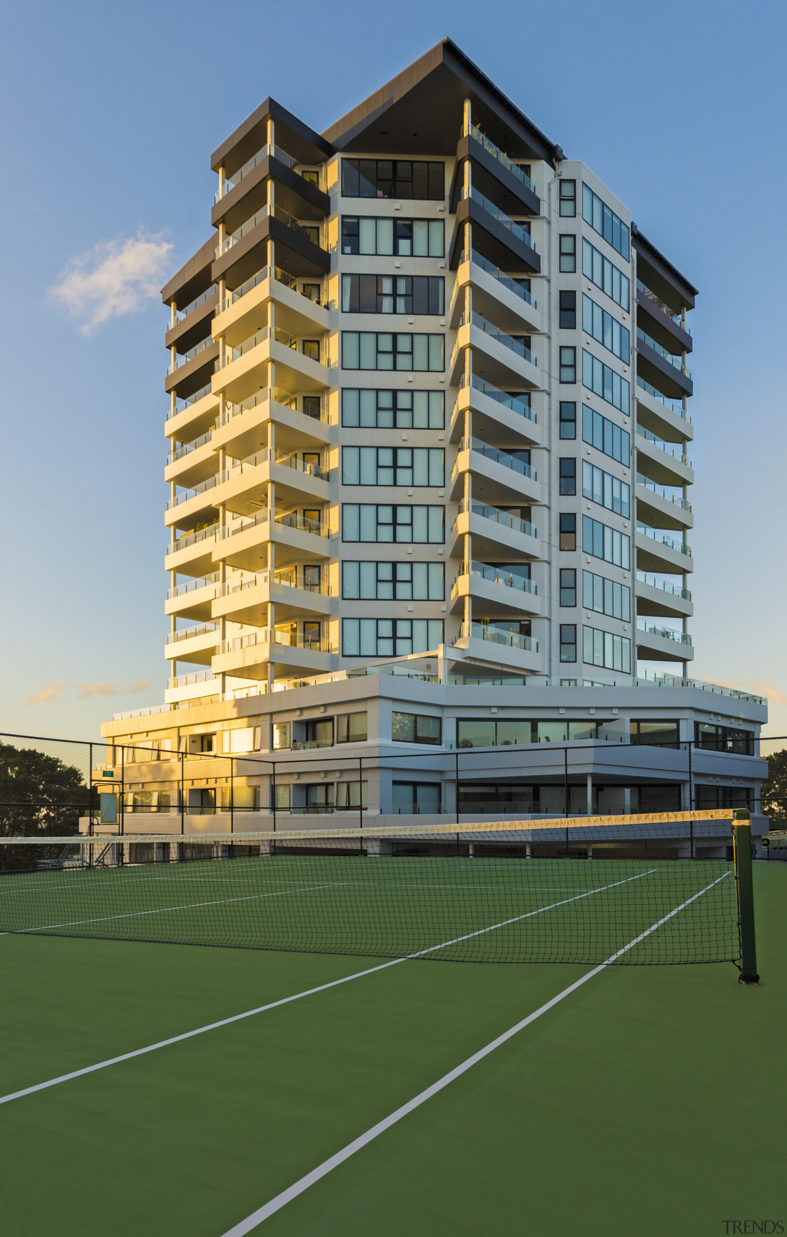 A tennis court attached to an original office apartment, architecture, building, city, commercial building, condominium, corporate headquarters, elevation, estate, facade, grass, headquarters, house, metropolitan area, mixed use, real estate, residential area, sky, structure, tower block, urban area, green, teal