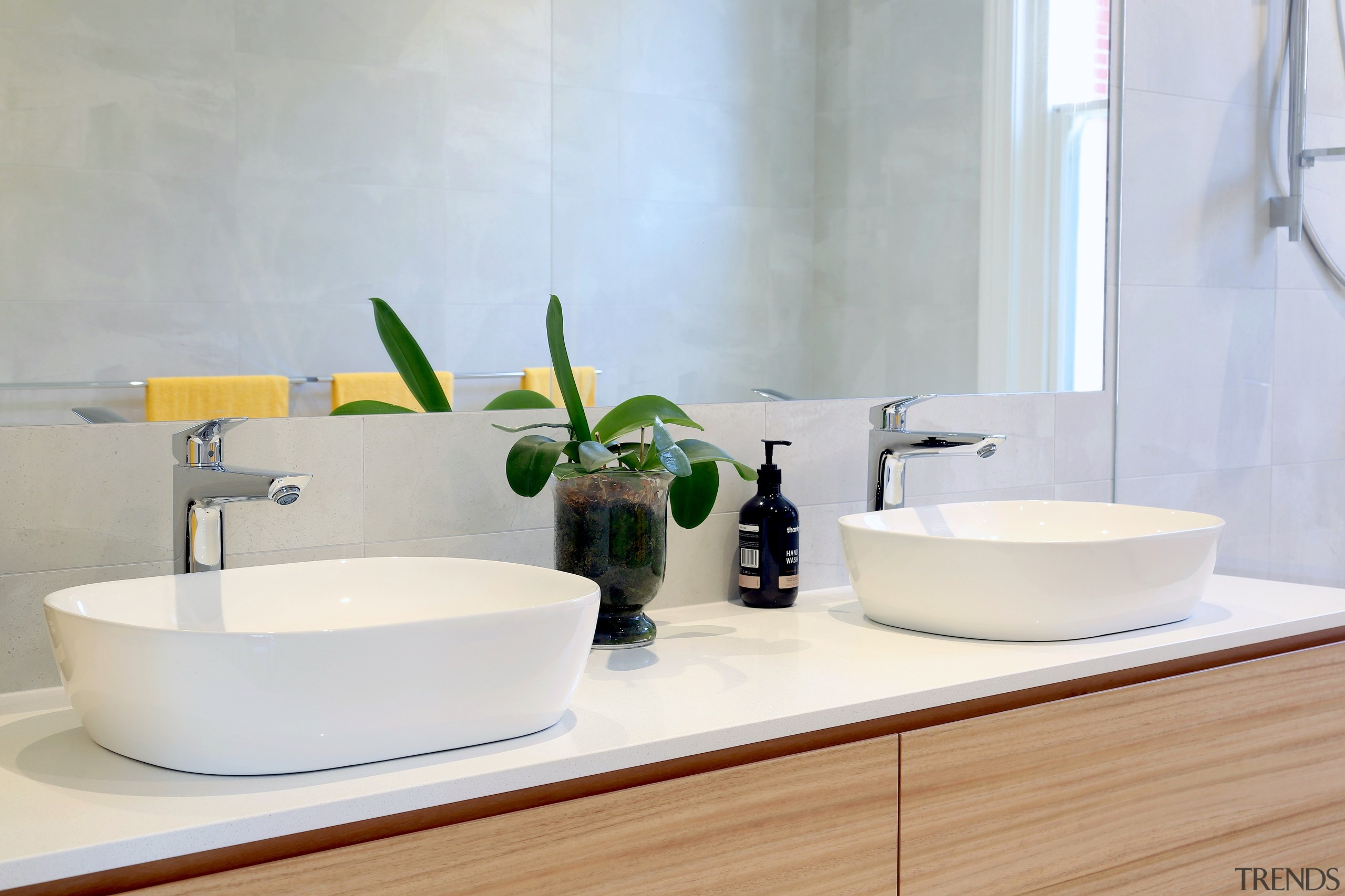 The contemporary design for this bathroom included tabletop architecture, bathroom, bathroom accessory, bathroom cabinet, bathroom sink, ceramic, countertop, floor, flooring, furniture, interior design, material property, plumbing fixture, product, property, room, sink, tap, tile, wall, white, white, gray