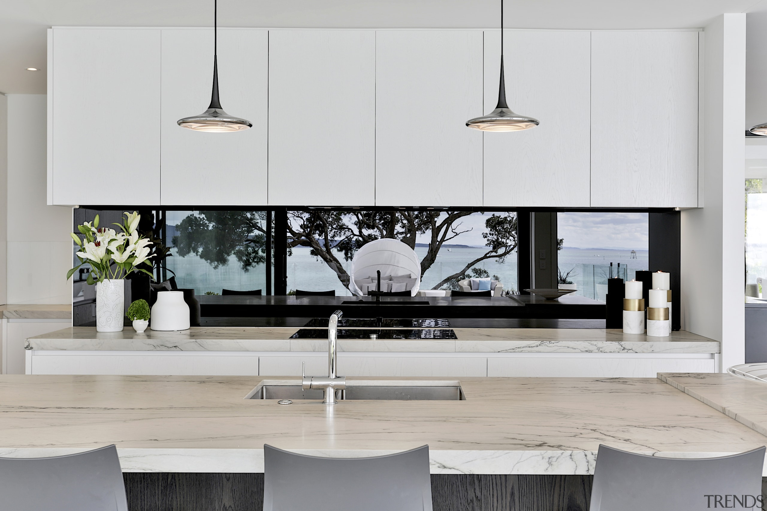 A glass mirrored splashback reflects harbour views for gray, white