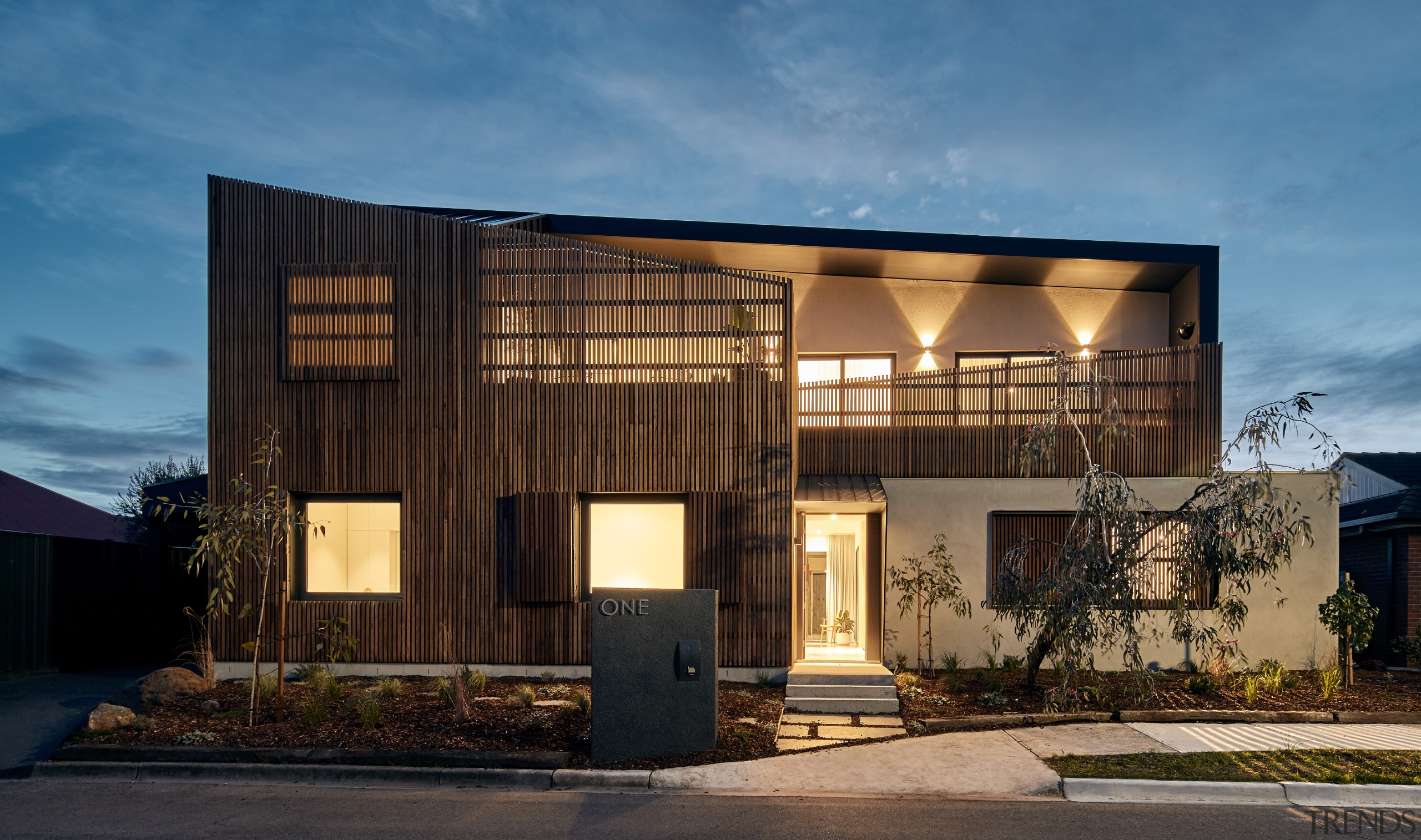 The Star Architecture-designed home at dusk. architecture, building, commercial building, design, facade, home, house, interior design, material property, mixed-use, property, real estate, residential area, sky, tree, black, teal