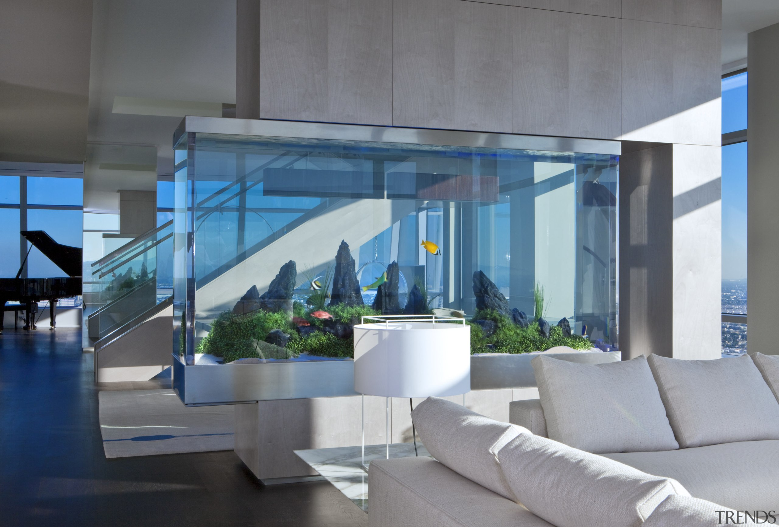 A large aquarium is a centerpiece in this architecture, condominium, daylighting, glass, home, house, interior design, lobby, real estate, gray