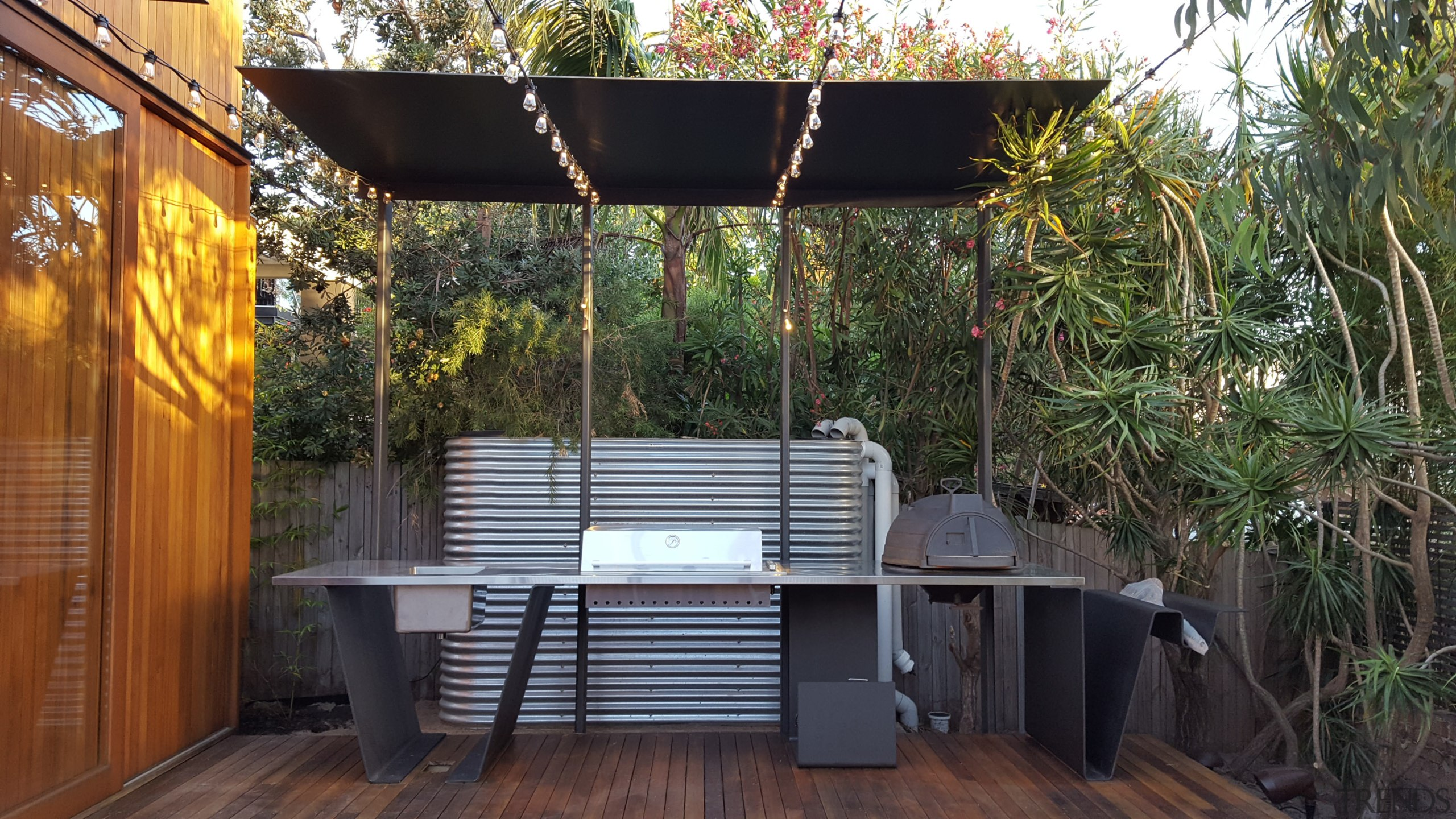 This custom-designed  outdoor cooking station includes a backyard, house, outdoor structure, patio, real estate, black