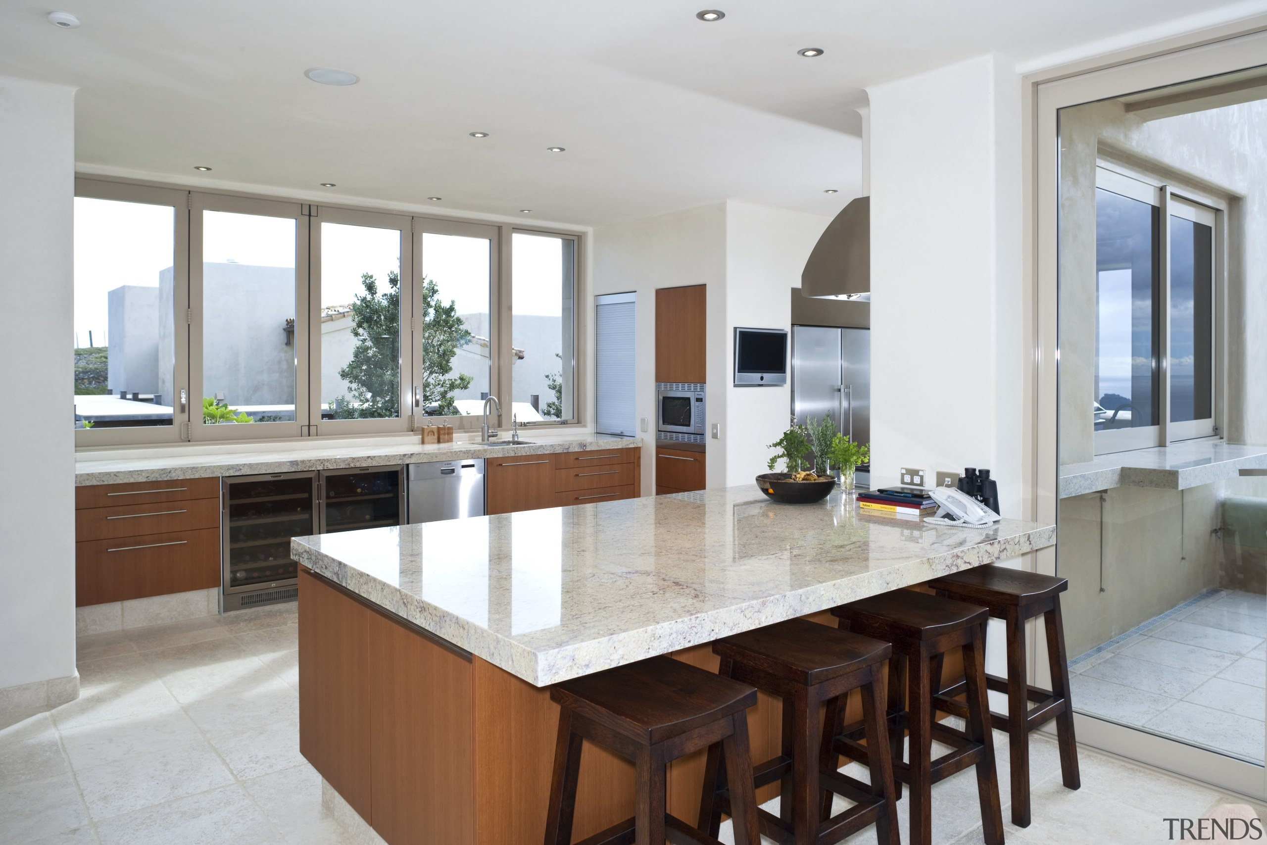 View of kitchen which features island, bar stools, cabinetry, countertop, cuisine classique, estate, interior design, kitchen, property, real estate, gray, white