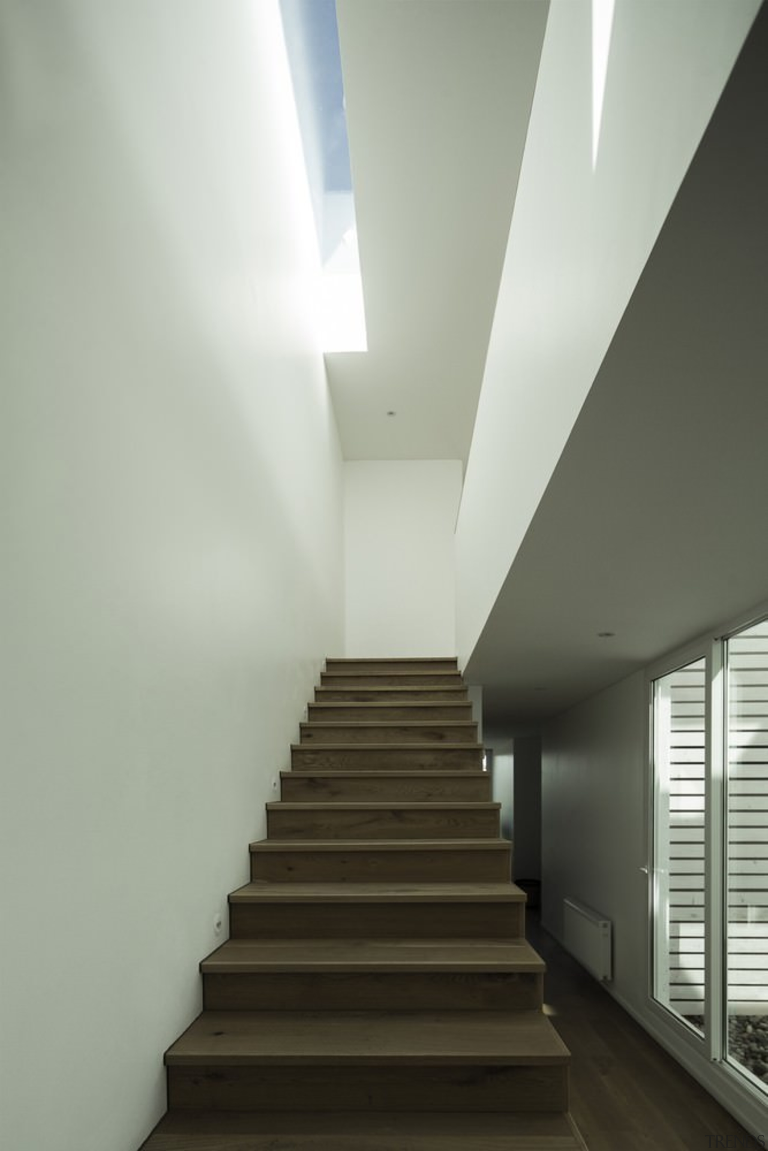 A skylight runs parallel to the stairway, illuminating architecture, ceiling, daylighting, handrail, house, interior design, stairs, gray, black