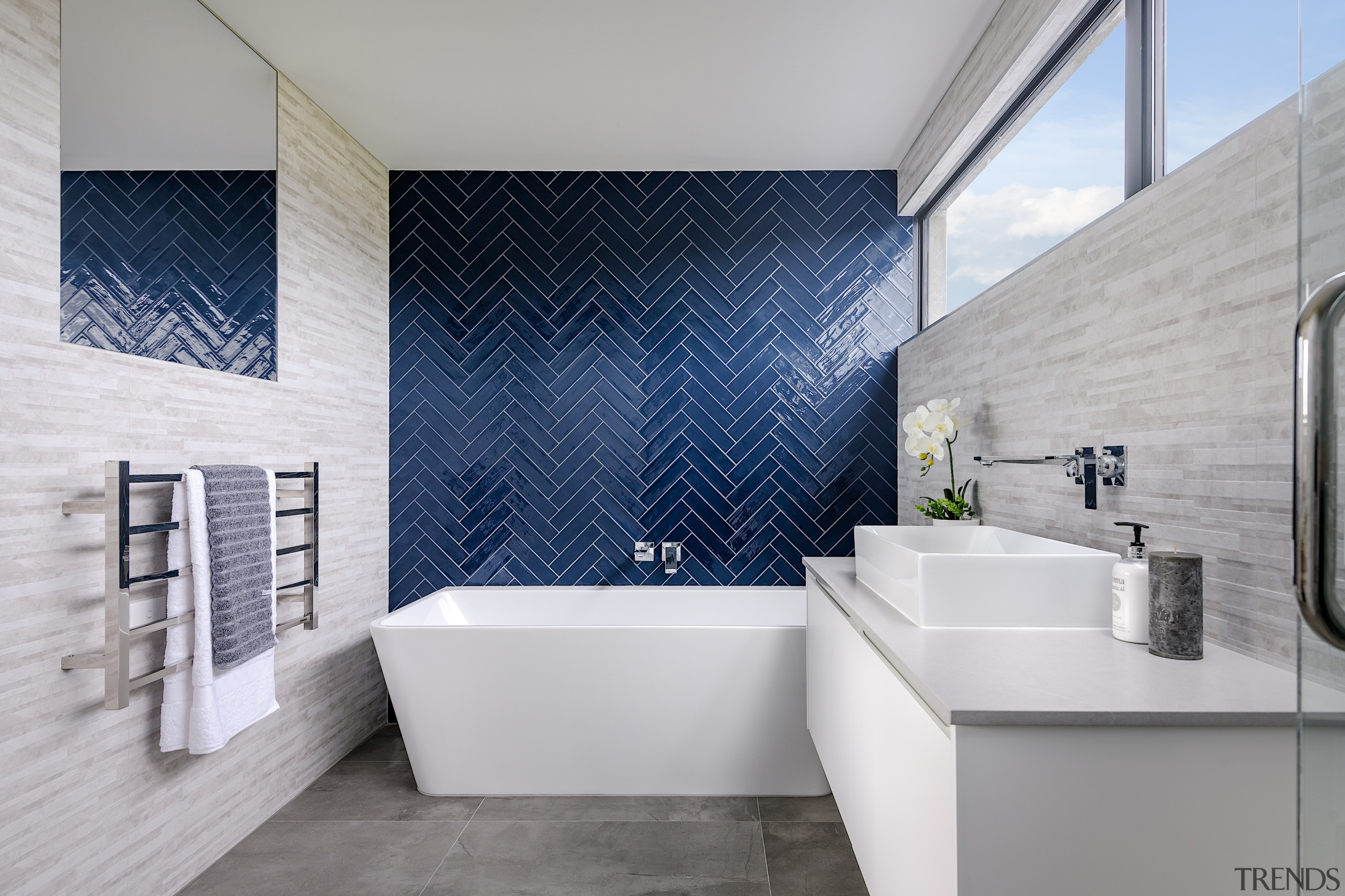 A bold feature wall of blue herringbone tiles