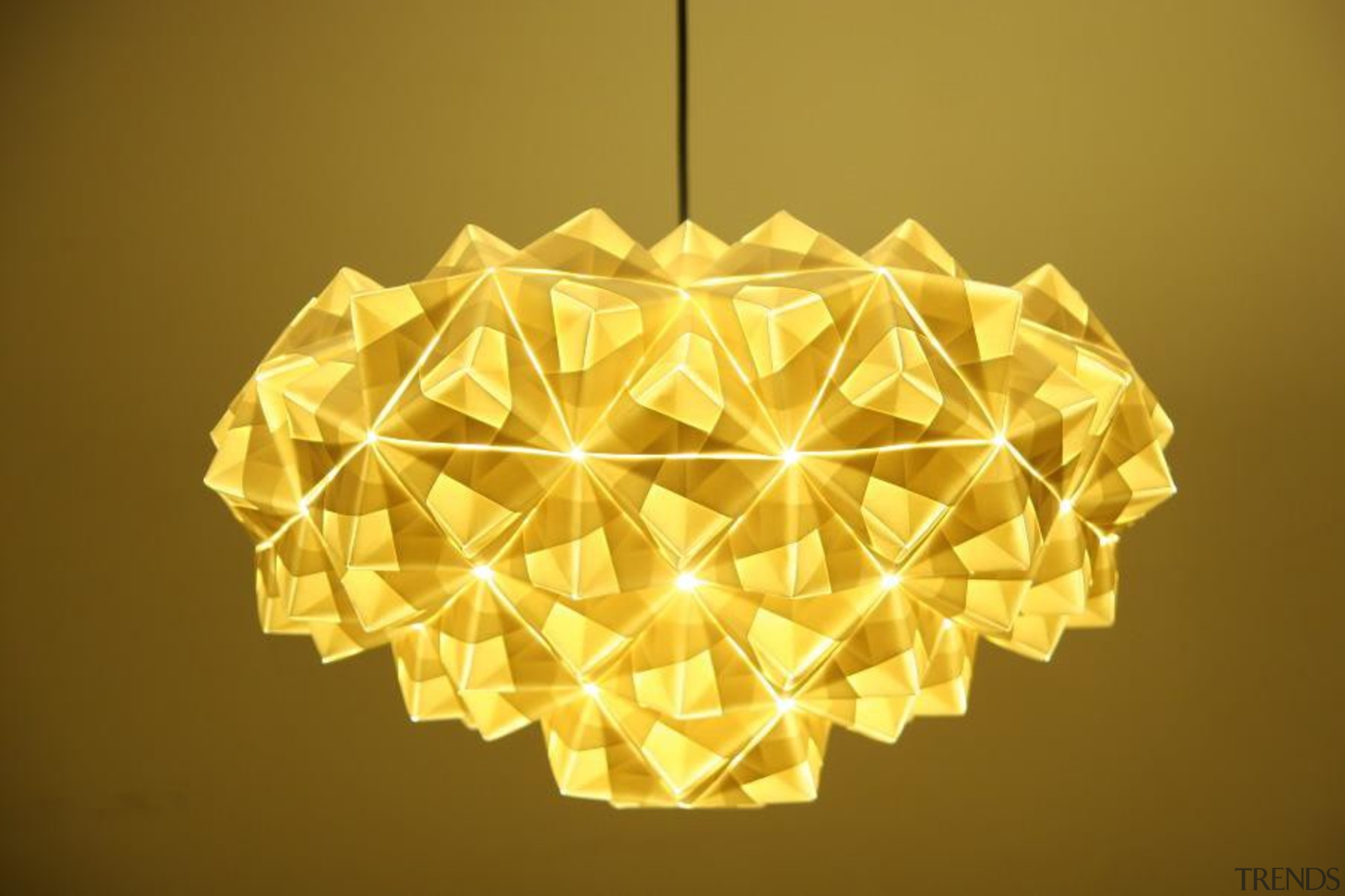 A range of folded metallic fabrics  are lampshade, light fixture, lighting, lighting accessory, origami, origami paper, product design, symmetry, yellow, brown, orange