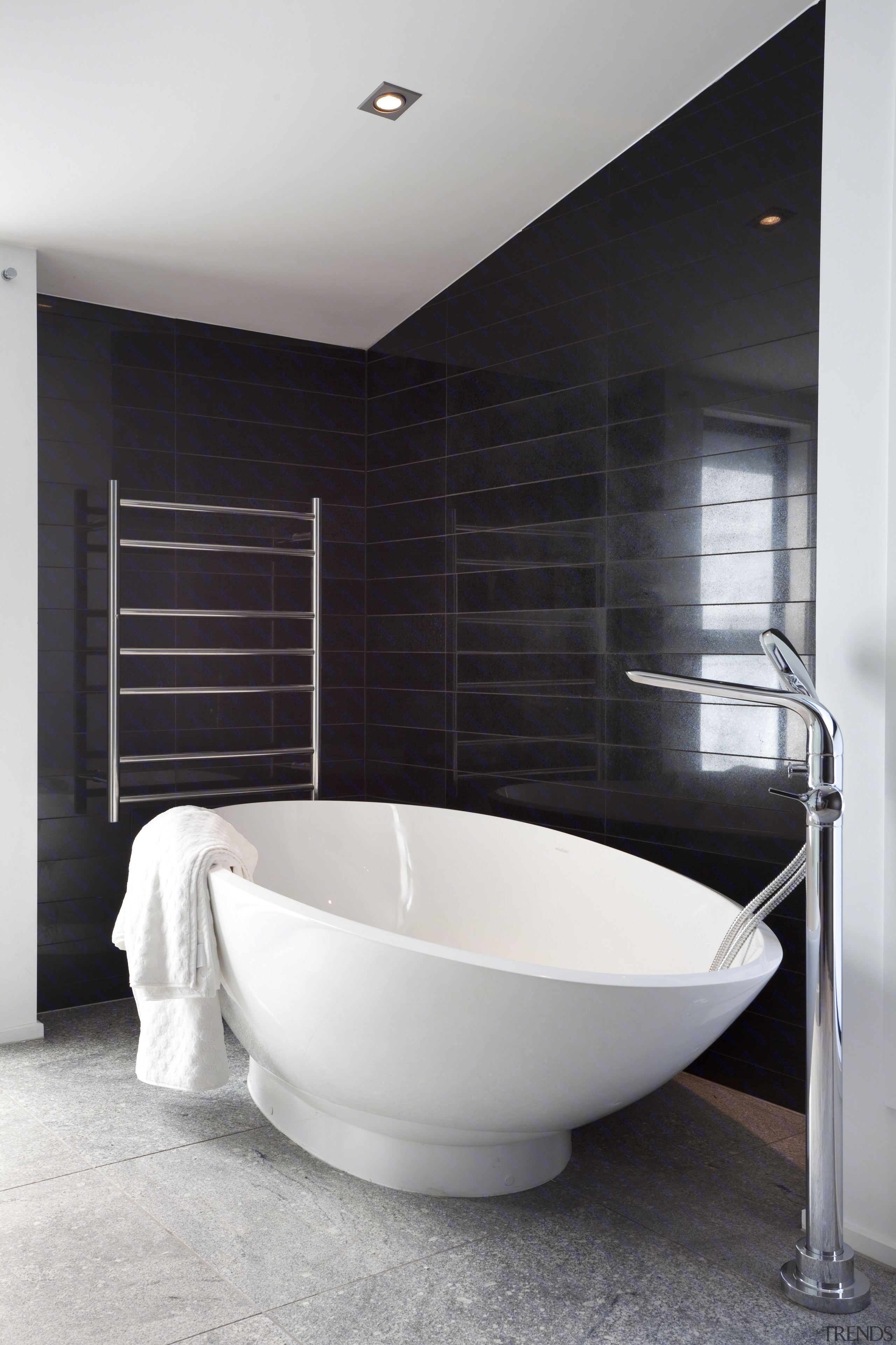 View Of Bathroom With Black Tiled Walls And Contemporary Oval