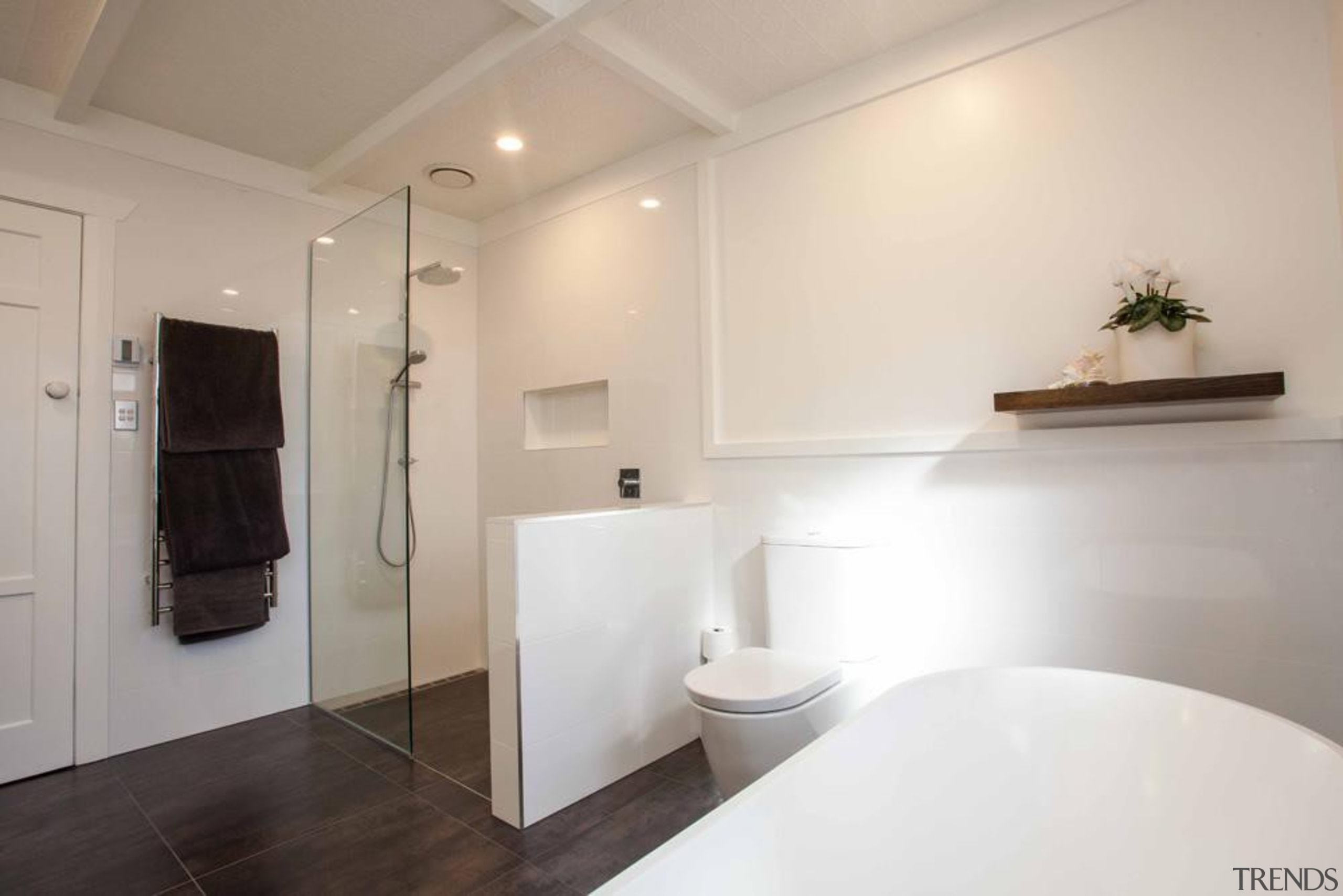 Dark flooring and cabinetry contrast the dominantly white bathroom, floor, home, interior design, property, real estate, room, sink, gray