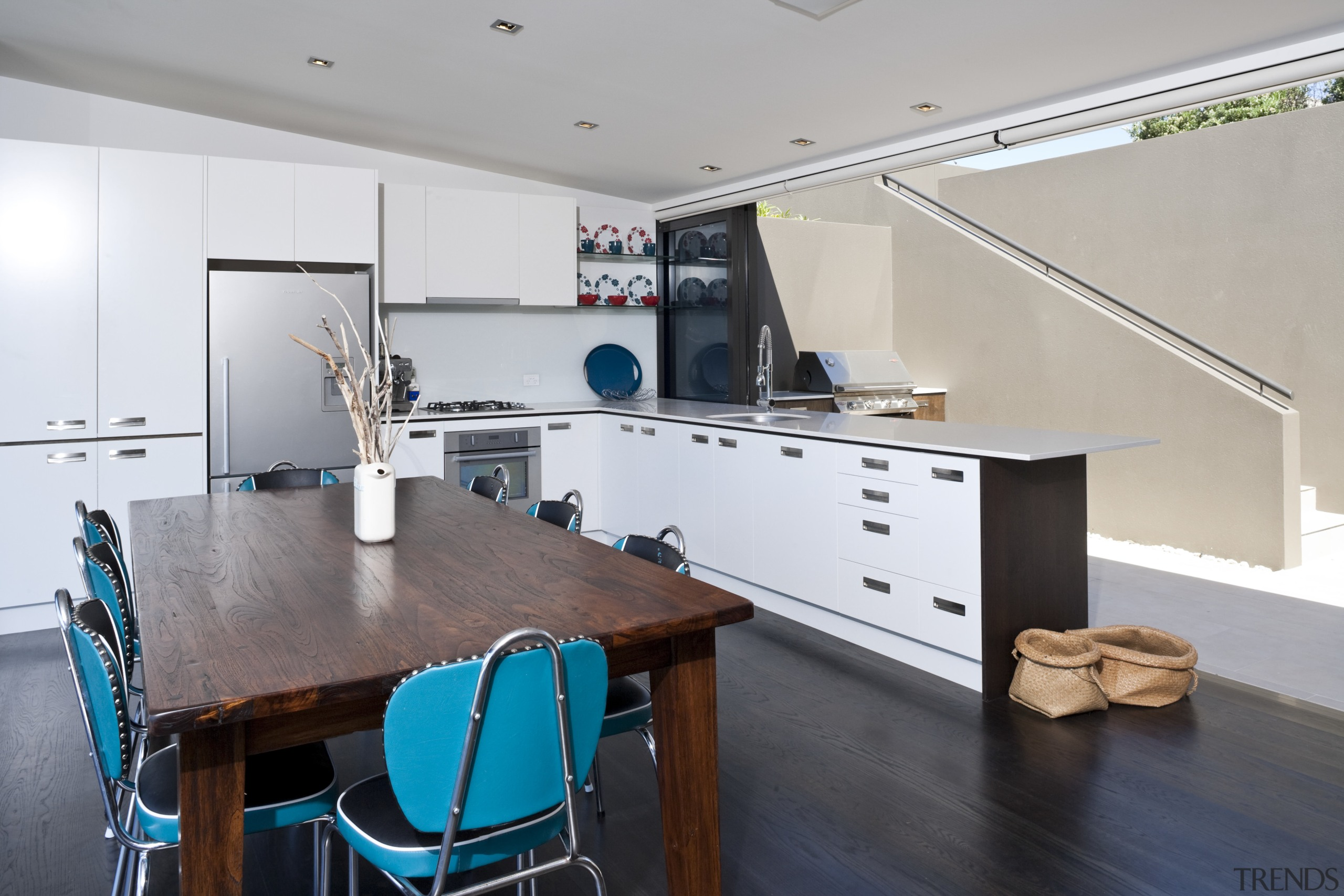 View of living space and kitchen featuring stained countertop, interior design, kitchen, room, table, gray, white