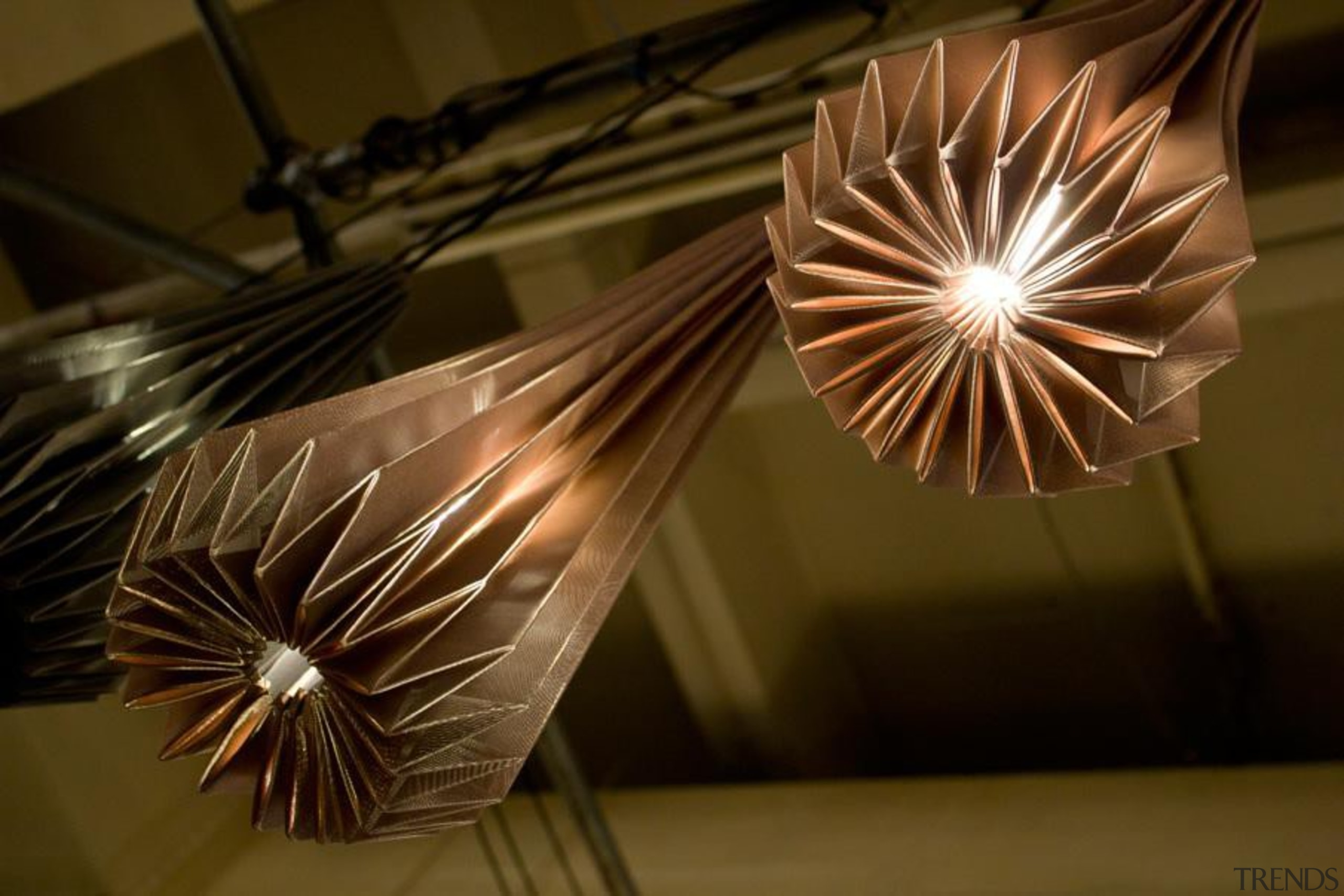 A range of folded metallic fabrics  are light, light fixture, lighting, lighting accessory, wood, brown