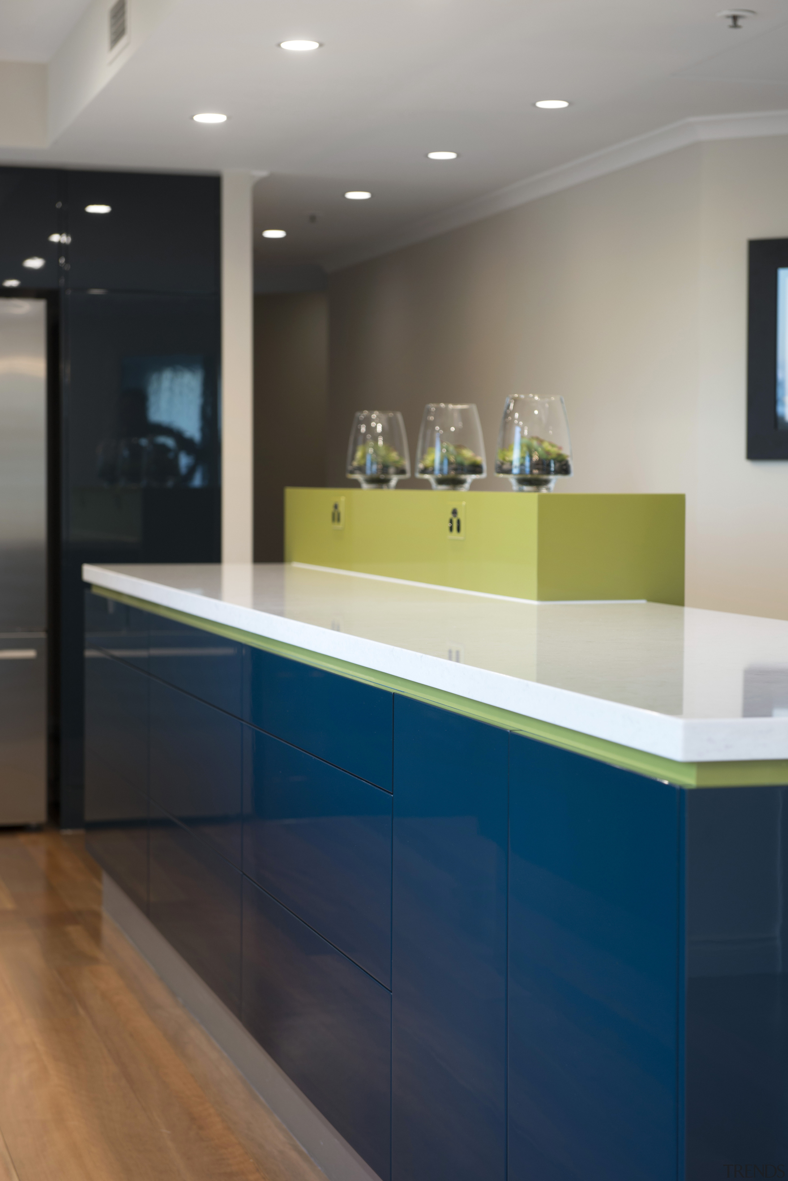 The raised front cabinet on the island provides architecture, bathroom, cabinetry, ceiling, countertop, floor, flooring, glass, interior design, kitchen, light, lighting, room, sink, gray
