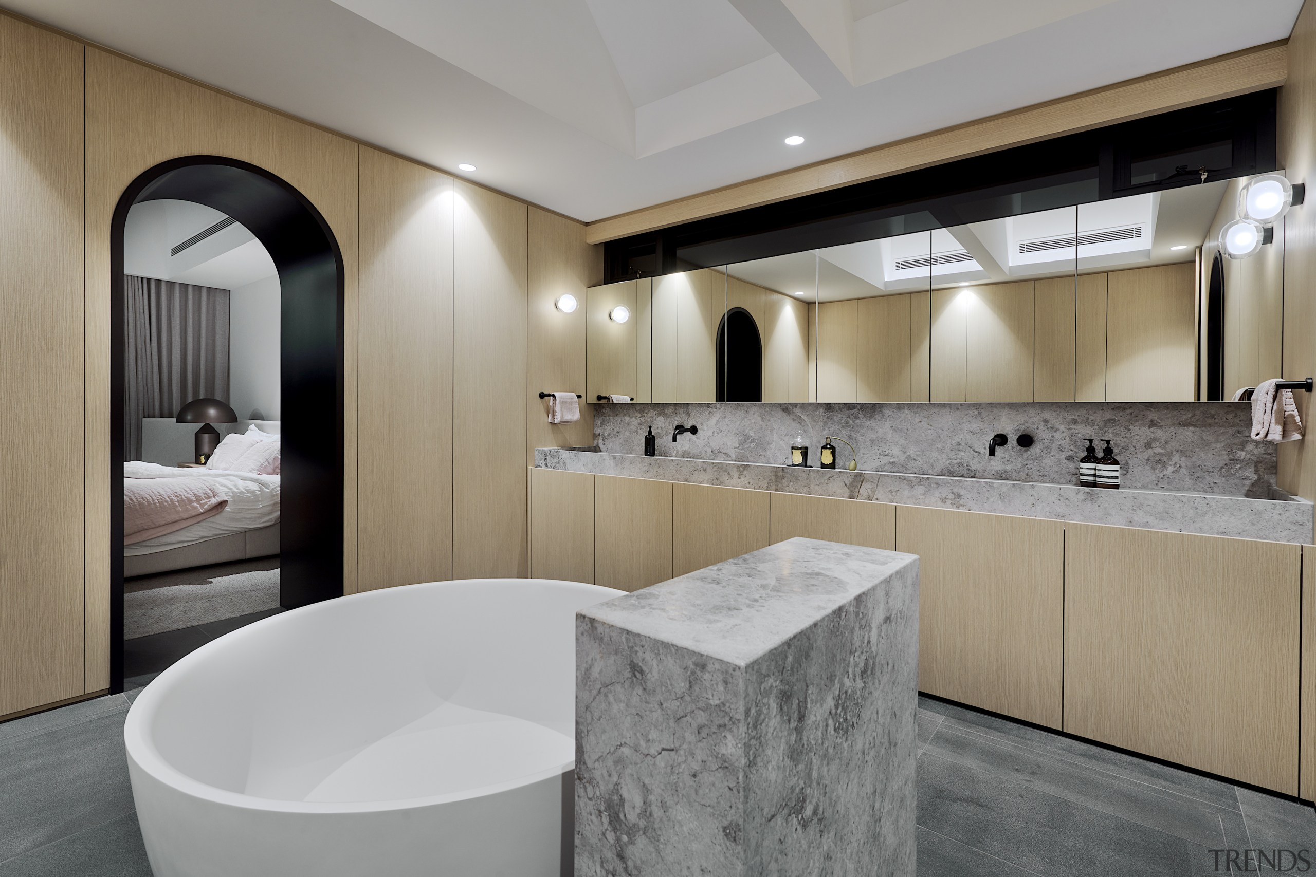 The blonde wood cabinetry and natural stone elements