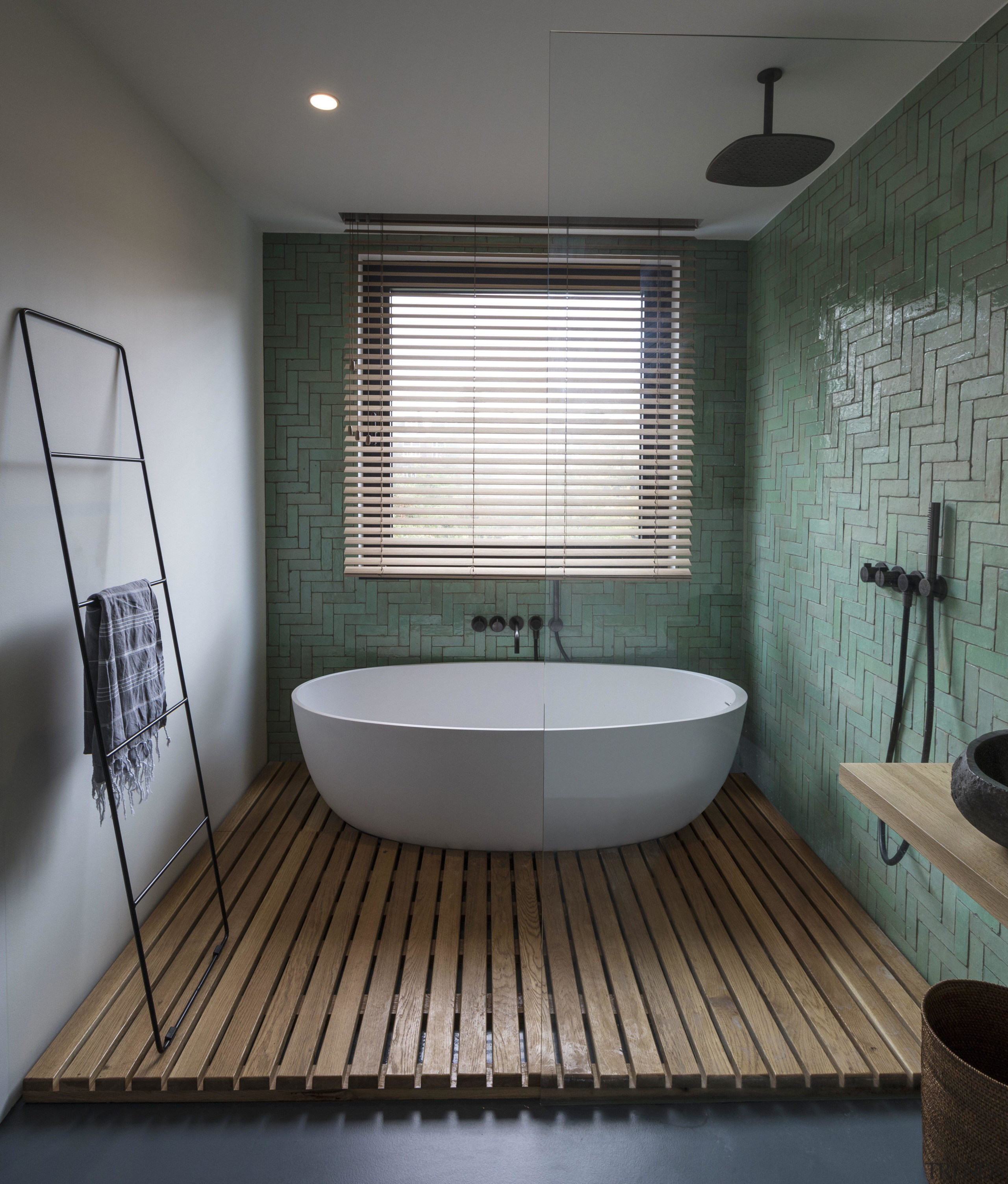 ​​​​​​​This bathroom's wet area containing the bath tub architecture, bathroom, bathtub, building, ceiling, daylighting, floor, flooring, furniture, hardwood, home, house, interior design, plumbing fixture, property, room, tile, wood flooring, gray, black