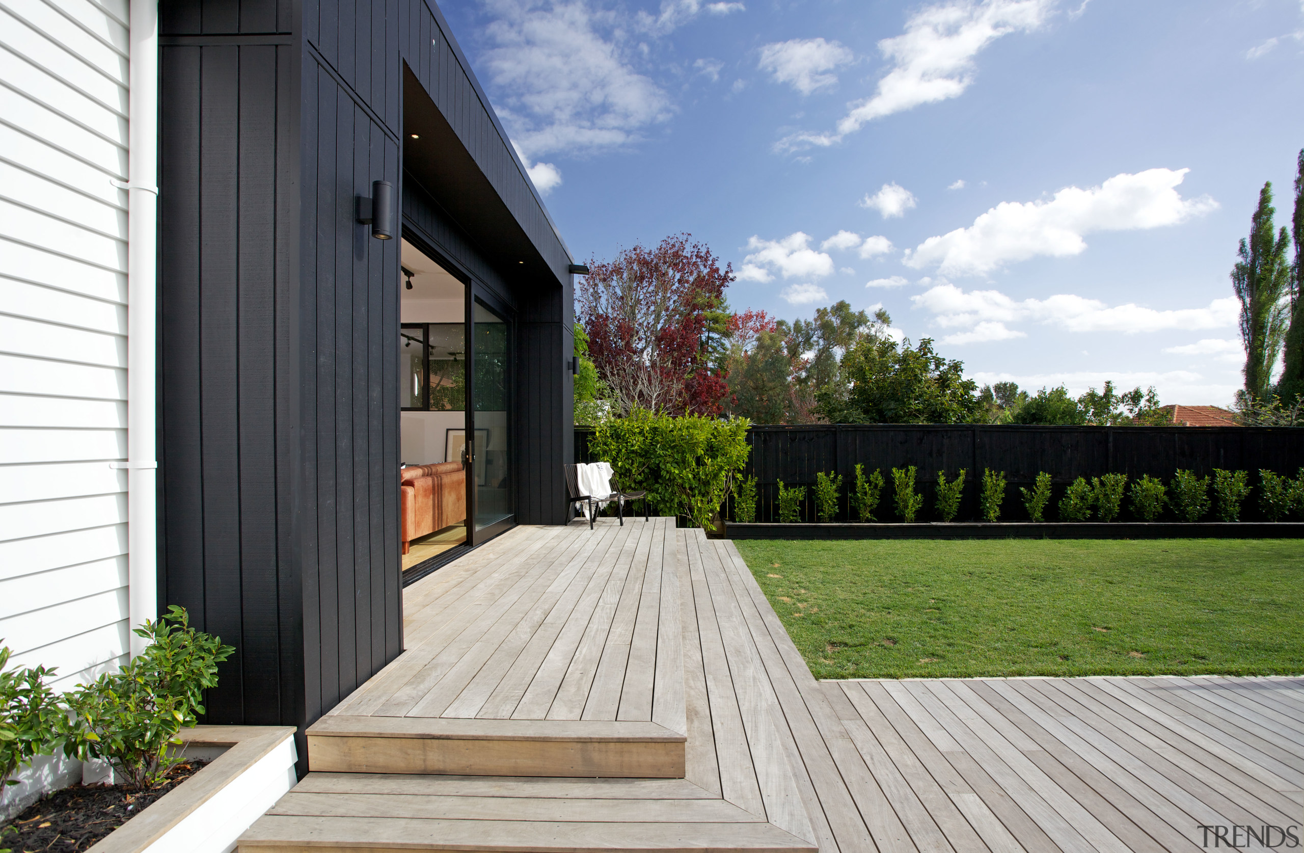 Contemporary black box addition to older home the architecture, backyard, cottage, deck, facade, grass, home, house, outdoor structure, property, real estate, residential area, siding, wood