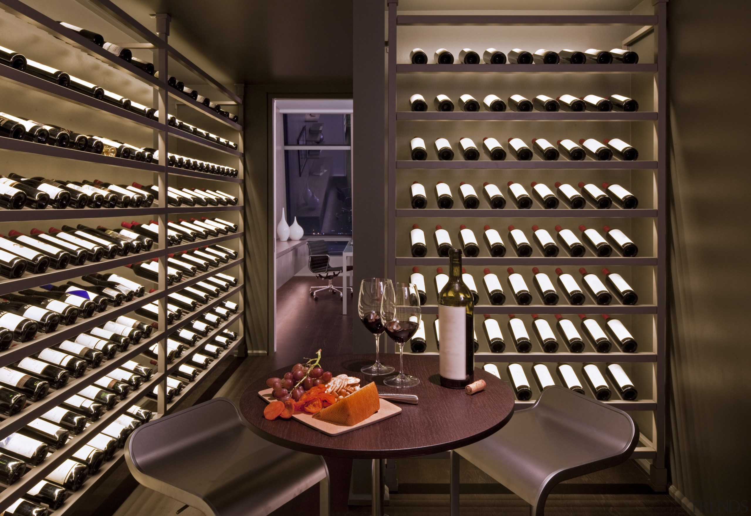 The climate-controlled wine cellar features custom, backlit wine interior design, wine cellar, winery, brown