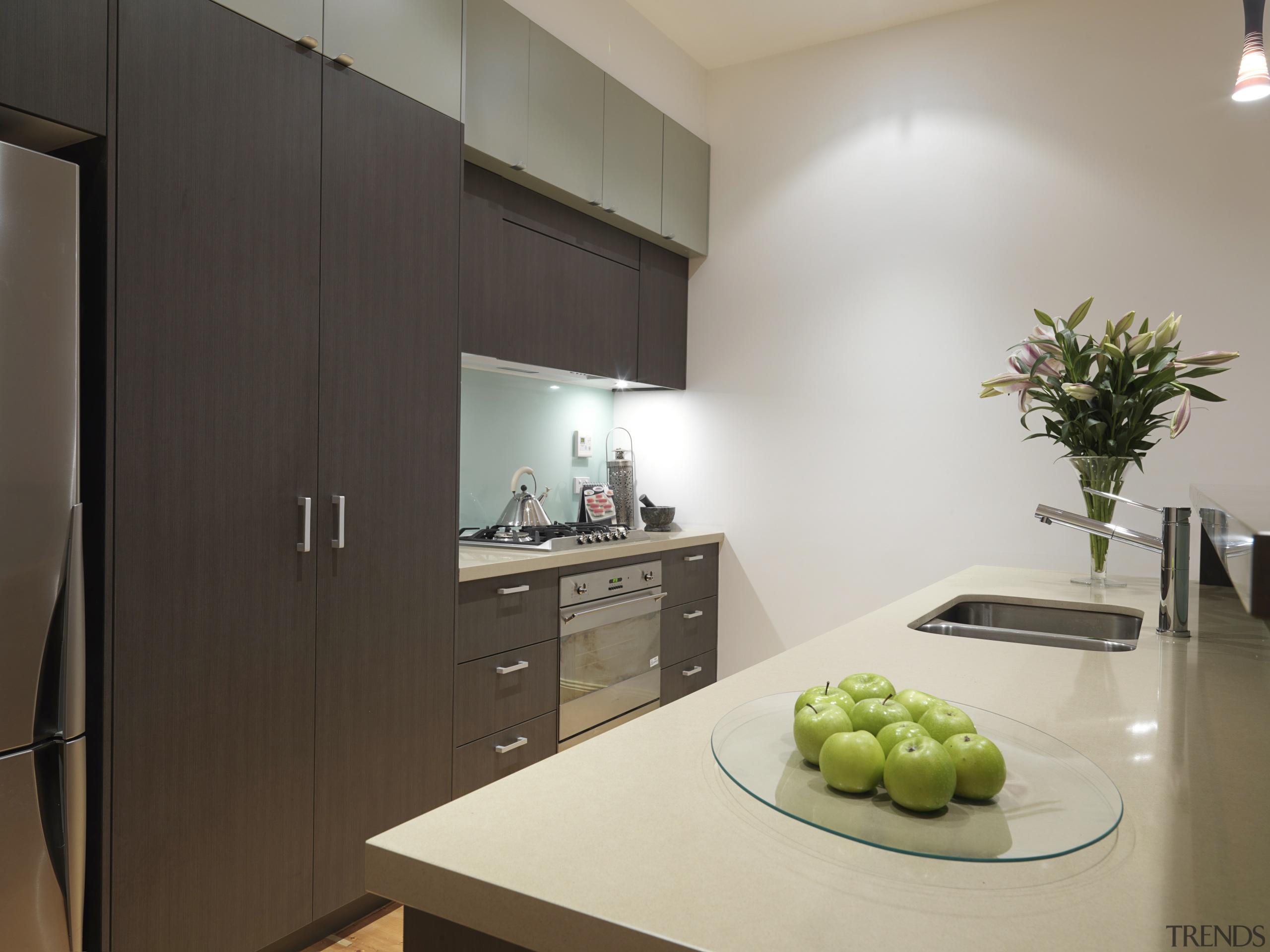 View of a kitchen featuring island, dark brown countertop, interior design, kitchen, real estate, room, gray, black
