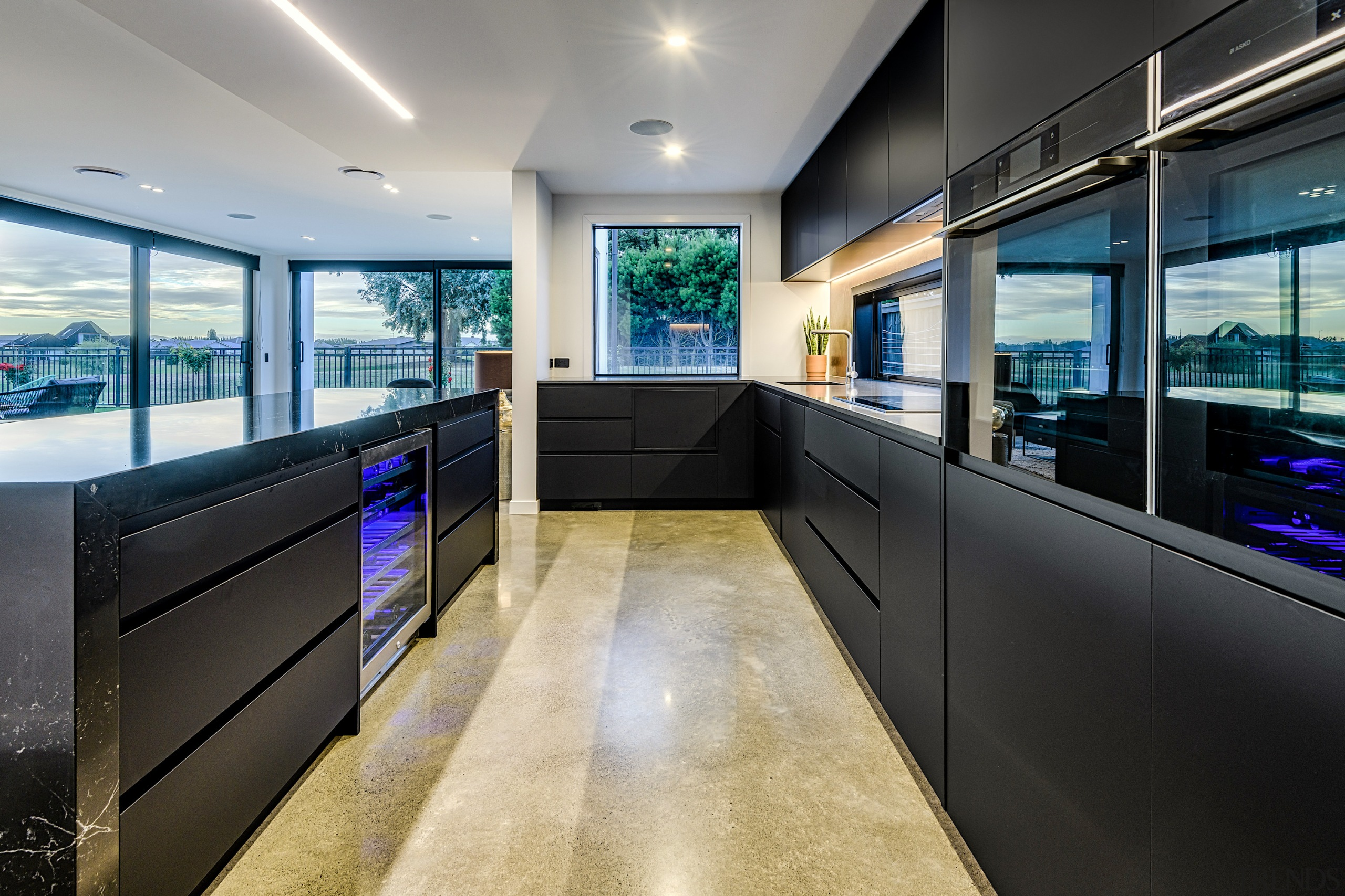 Stained concrete provides a solid anchor for this architecture, building, ceiling, countertop, design, floor, flooring, furniture, glass, home, house, interior design, lighting, office, property, real estate, room, black, gray