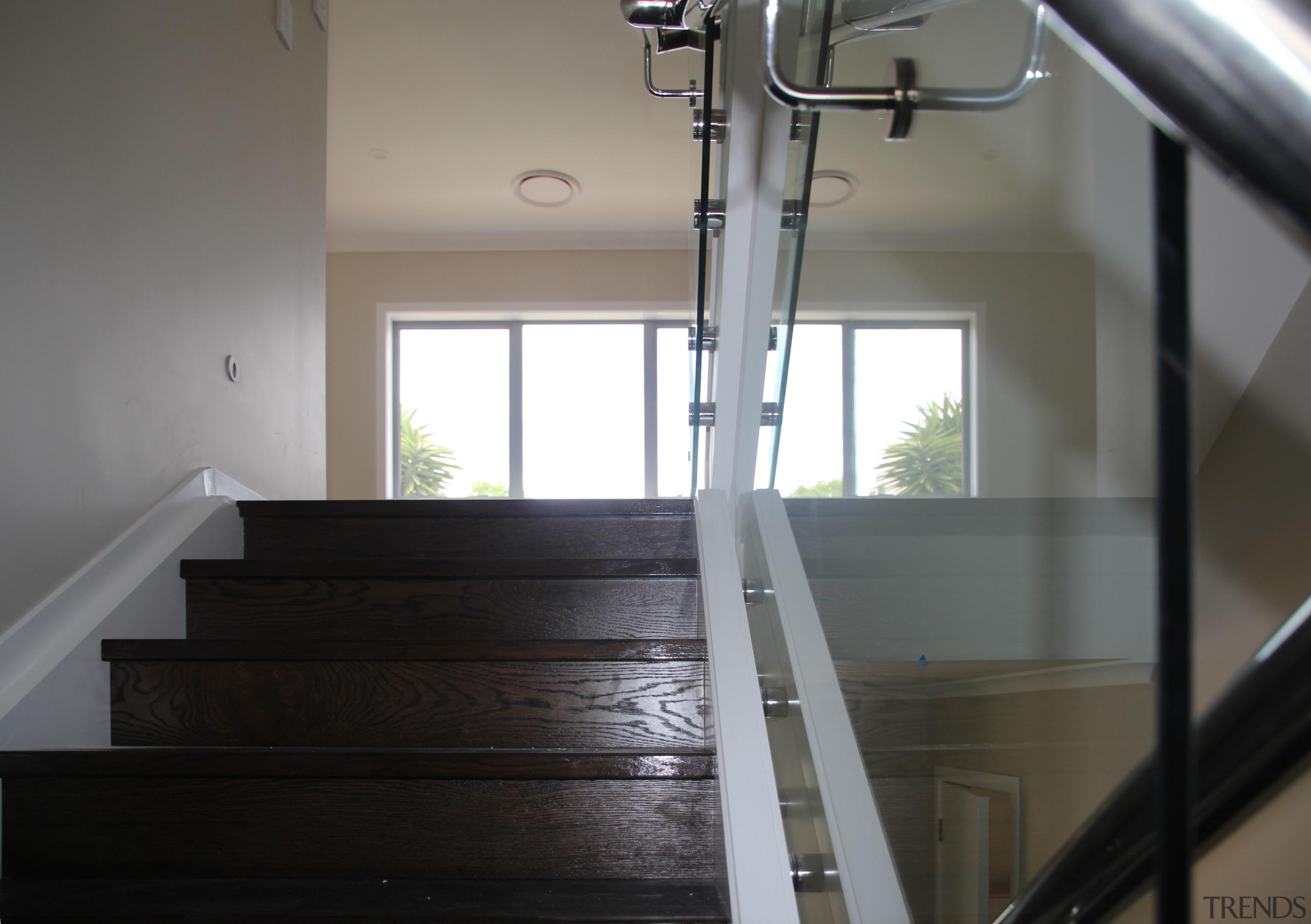This home features an engineered dark oak staircase daylighting, floor, flooring, glass, handrail, hardwood, house, stairs, wood, gray, black