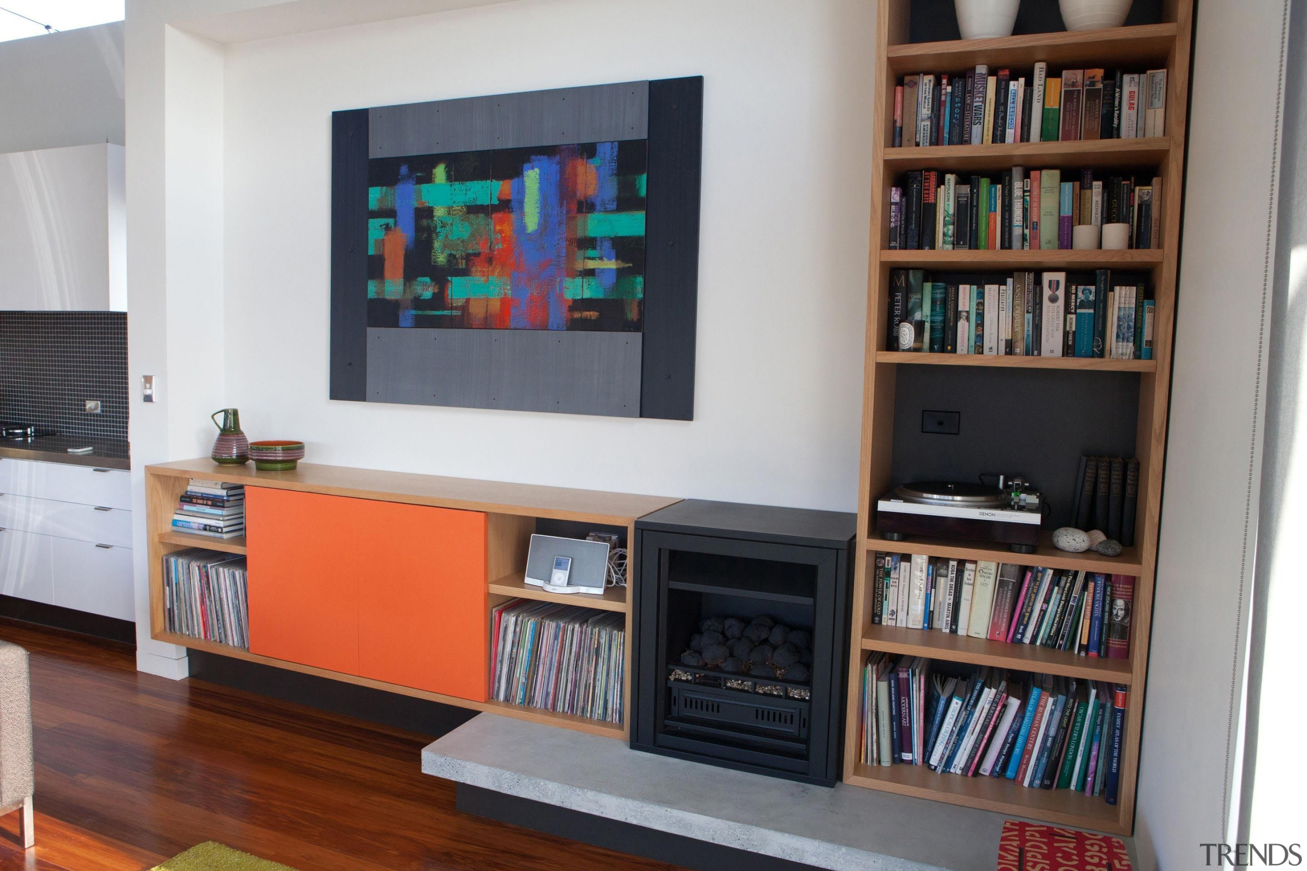 The new gas fireplace integrates seemlessly with the bookcase, furniture, interior design, library, living room, shelf, shelving, gray