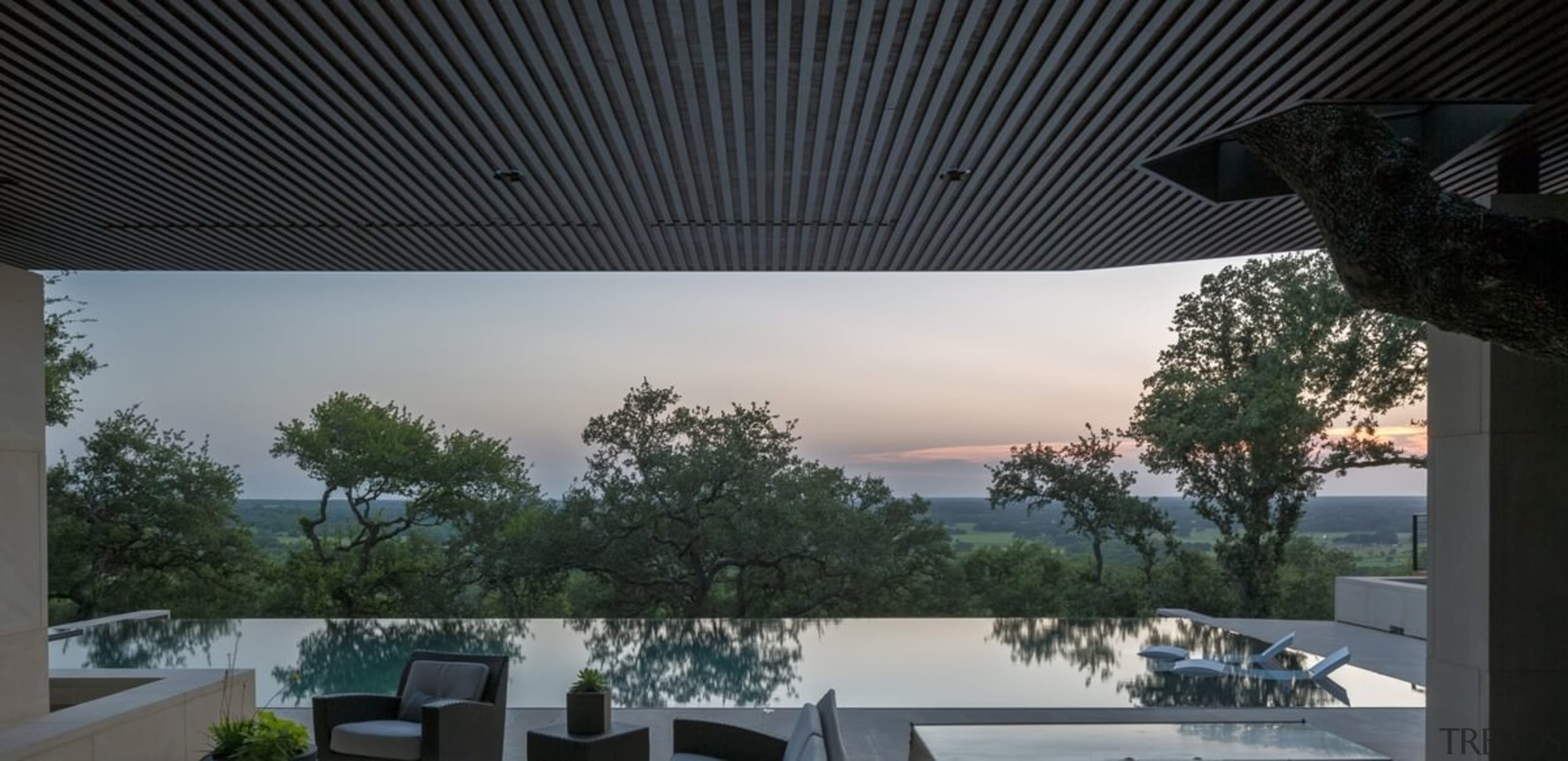 The tree line seems to rise up out architecture, daylighting, home, house, interior design, property, real estate, roof, shade, sky, window, black, gray