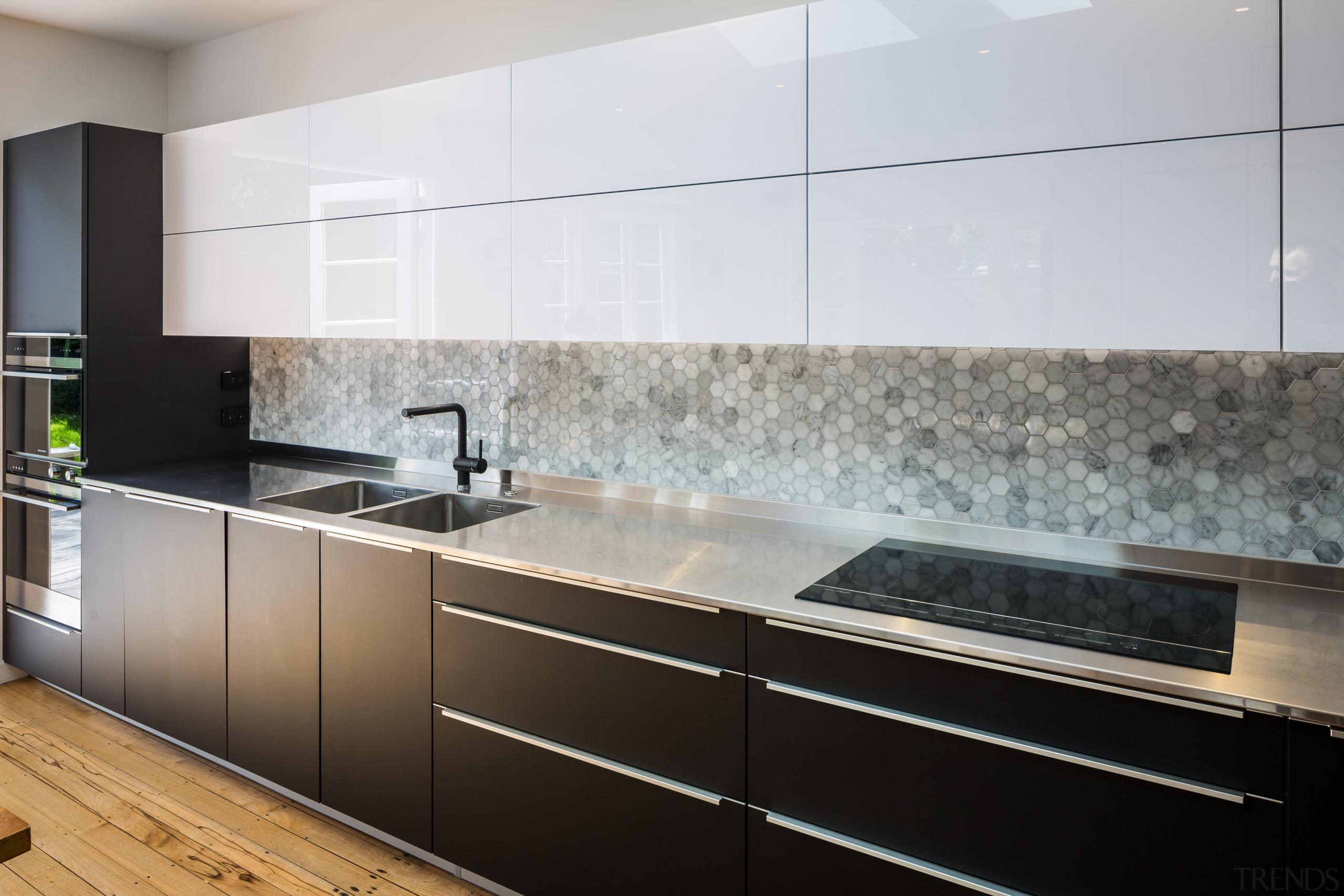 Hexagonal tiles make up the long splashback - cabinetry, countertop, floor, interior design, kitchen, product design, gray, black, white