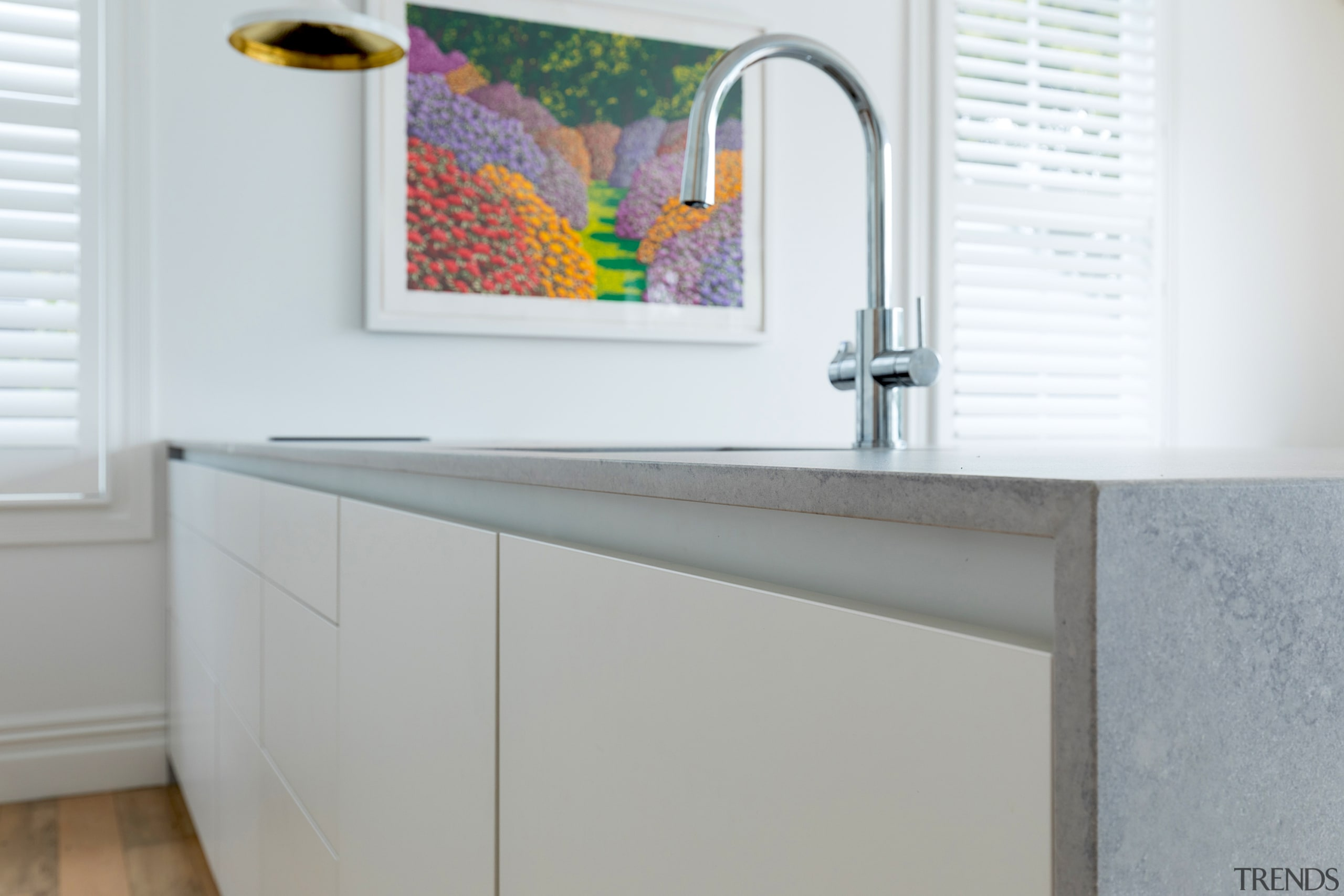 Slender, waterfall-end benchtops add to the kitchen's contemporary gray, white