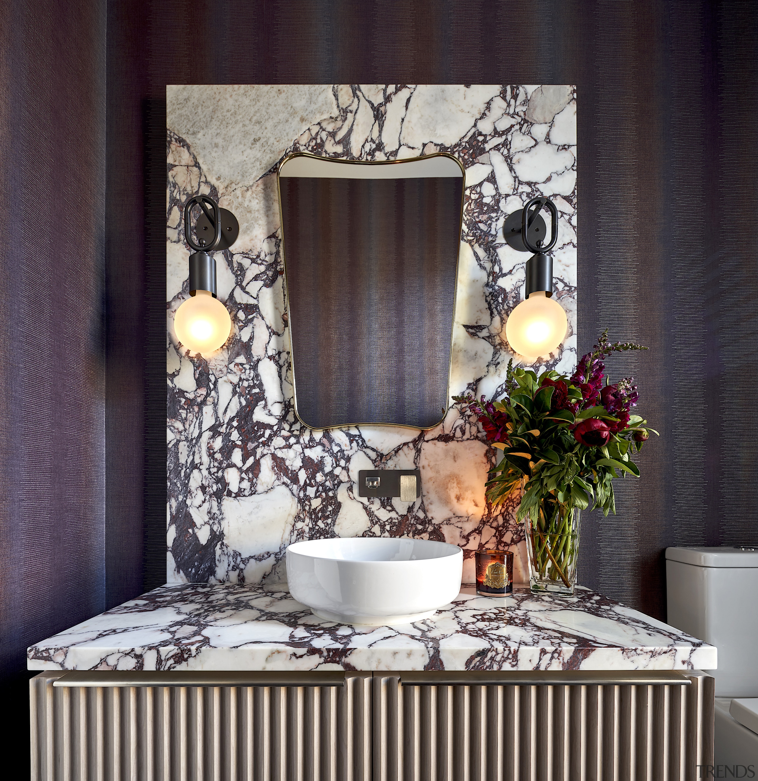 Vibrantly veined stone slabs and striking vinyl-faced wallpaper