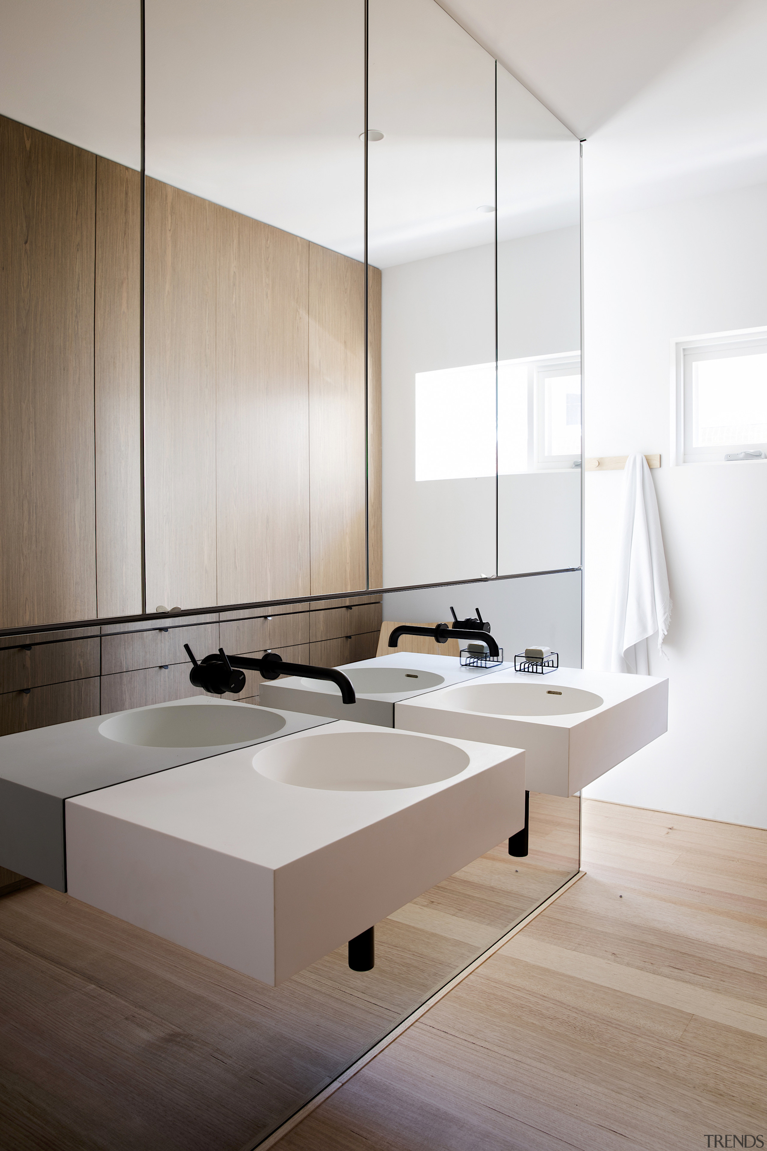 A mirror wall behind the two cantilevered sinks