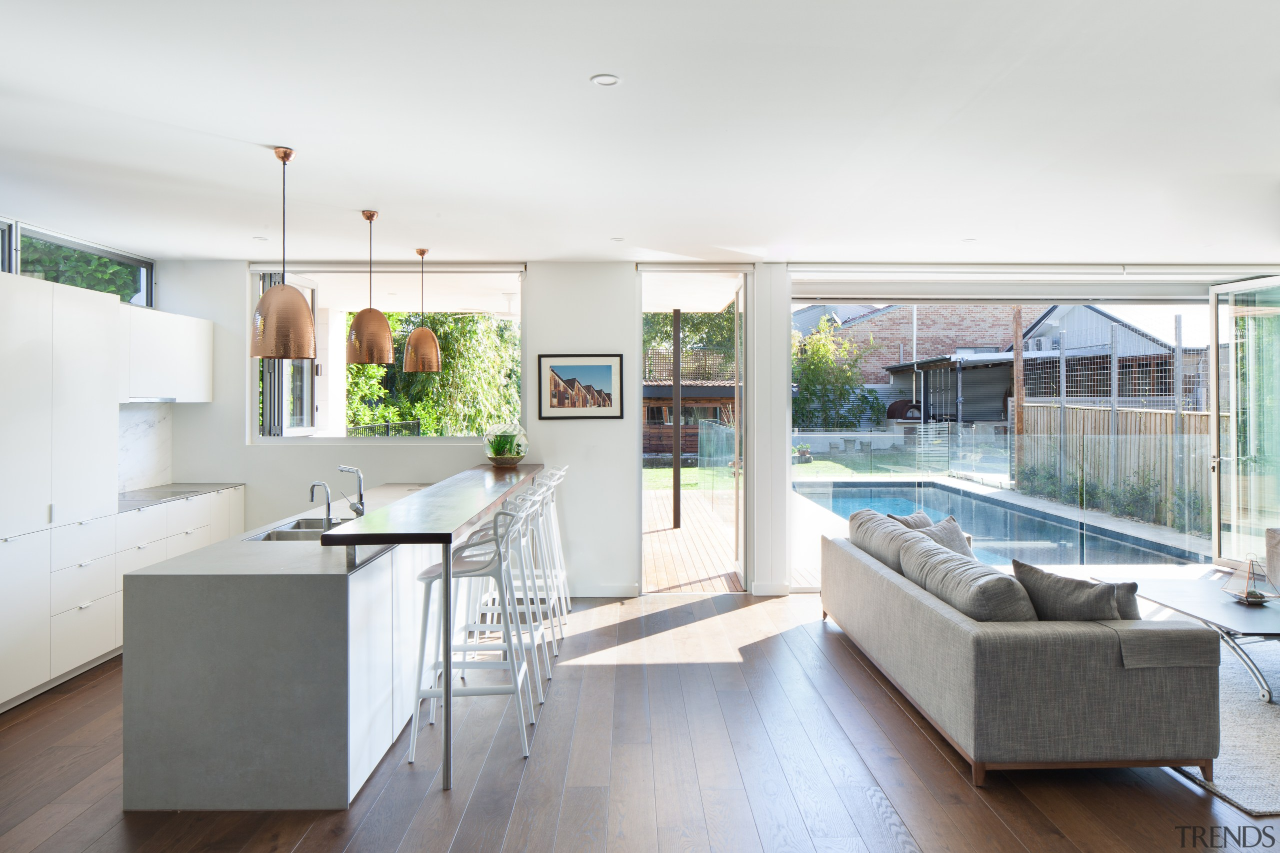 Light-filled and well-connected, this kitchen forms part of apartment, architecture, building, cabinetry, ceiling, countertop, daylighting, design, floor, flooring, furniture, hardwood, home, house, interior design, kitchen, living room, loft, property, real estate, residential area, roof, room, table, window, wood flooring, white
