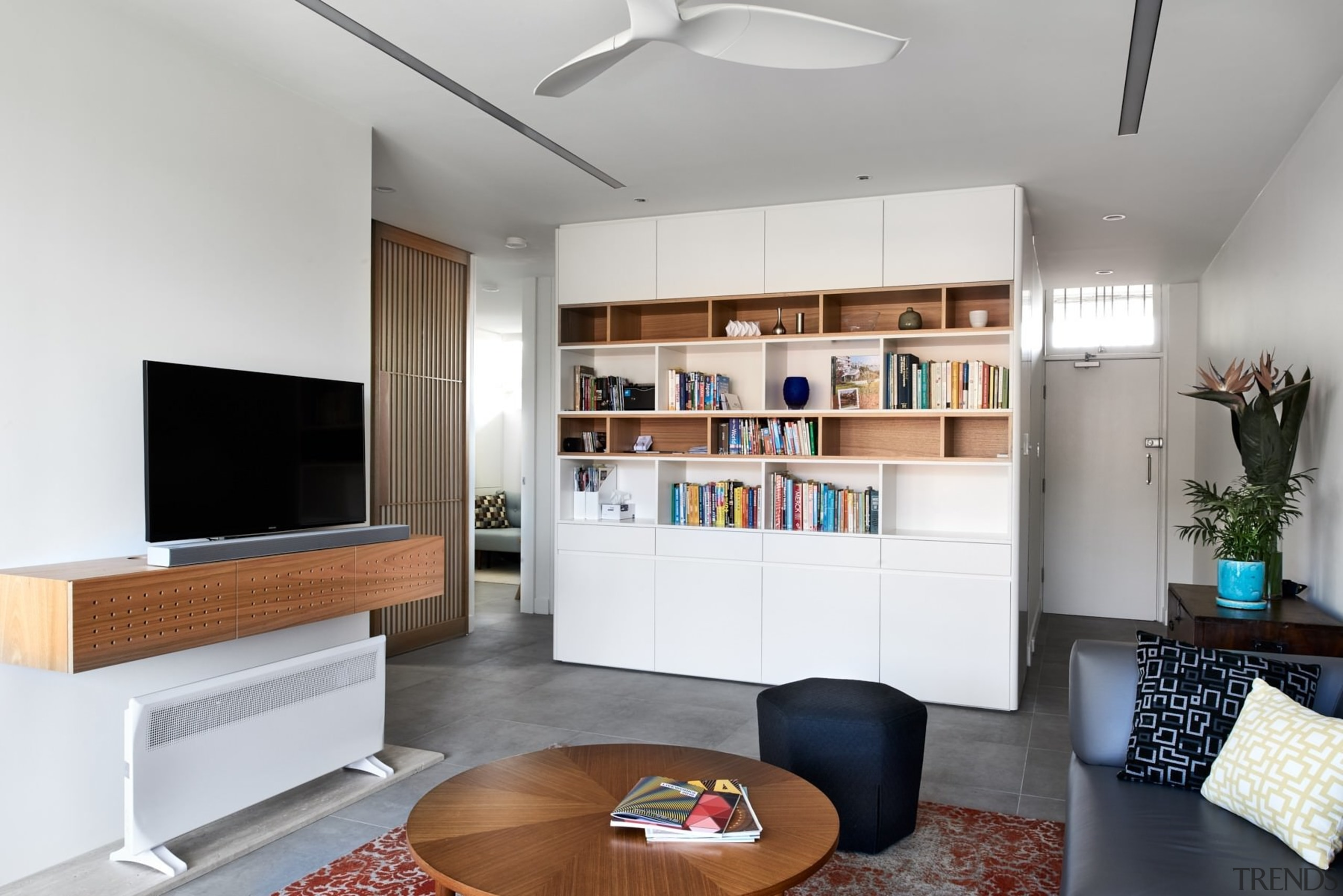 The living room feels spacious thanks to the furniture, interior design, interior designer, living room, room, shelving, gray