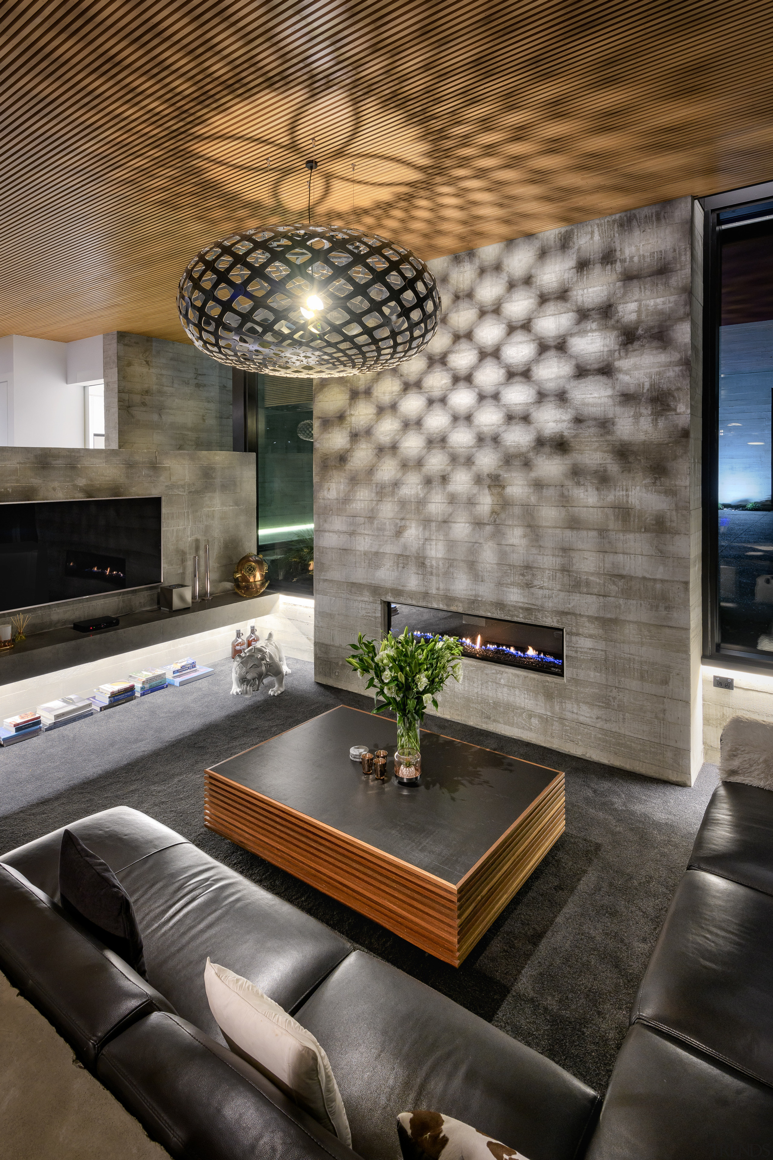 A designer lamp throws eye-catching patterns on the architecture, brick, building, ceiling, coffee table, design, floor, flooring, furniture, home, house, interior design, lighting, living room, property, real estate, room, table, tile, wall, gray, black