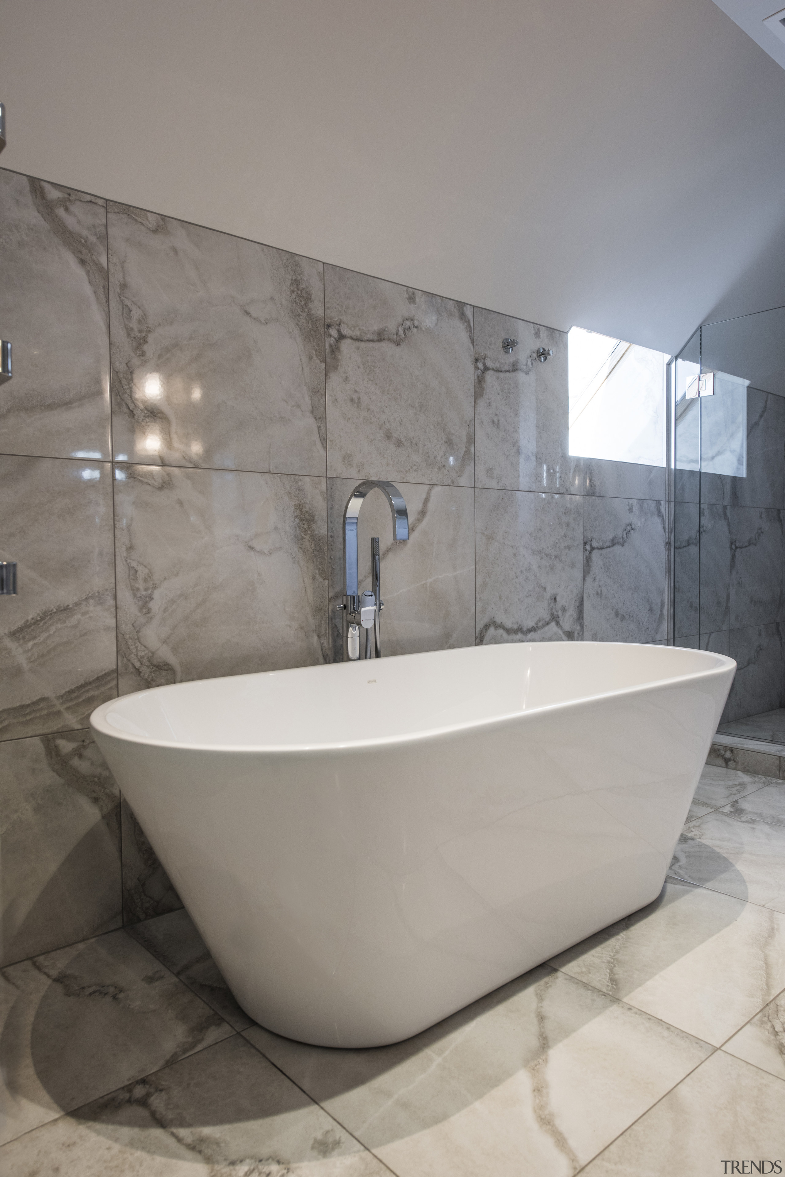 The bath was selected for its play on architecture, bathroom, bathtub, ceramic, floor, flooring, home, house, interior design, limestone, marble, material property, plumbing fixture, property, room, tap, tile, wall, gray