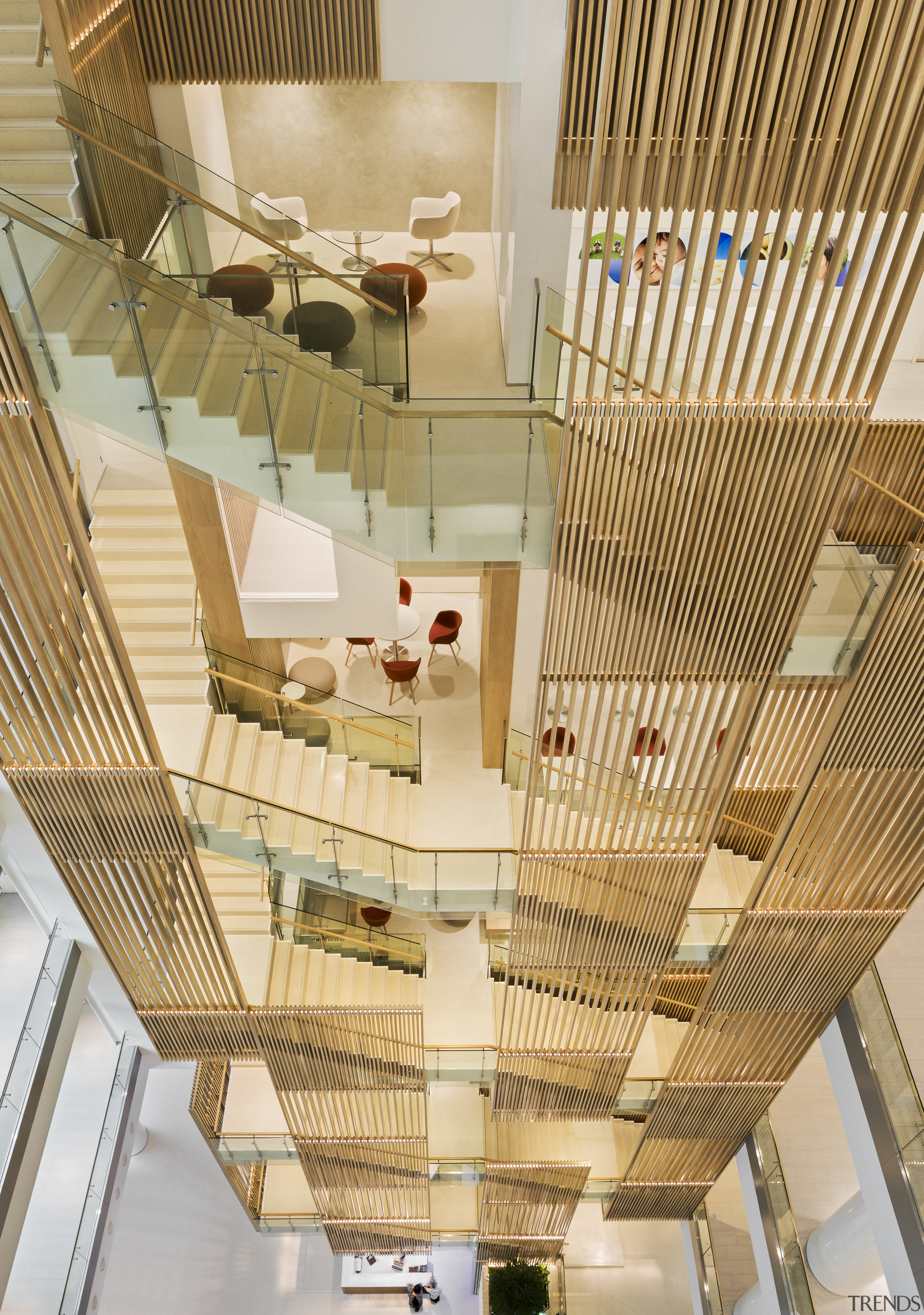 The staircase running through the atrium of this architecture, ceiling, daylighting, home, interior design, stairs, wood, orange, brown