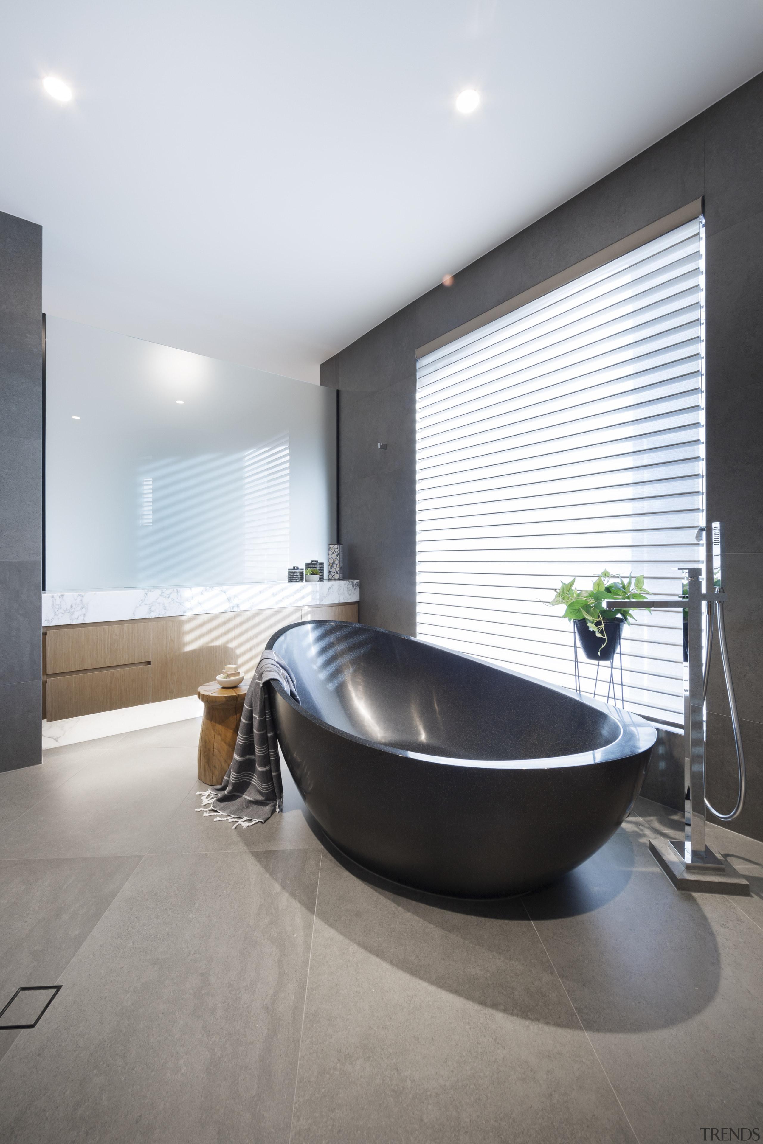 This black Apaiser freestanding bath tub sits on white, gray